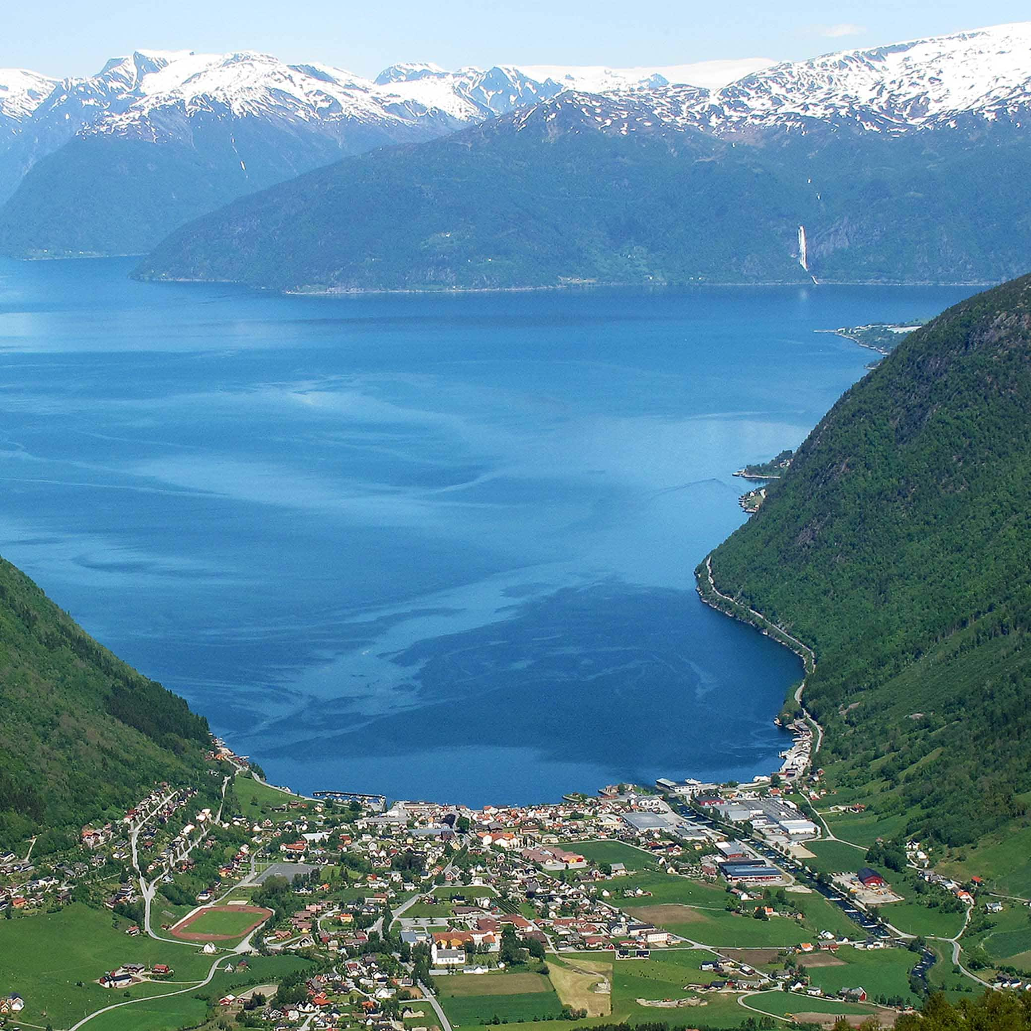 A view of Vik from the famous viewpoint Storesvingen where you see the small village of Vik bordering the waters of the Sognefjord with snowcapped mountains in the background.