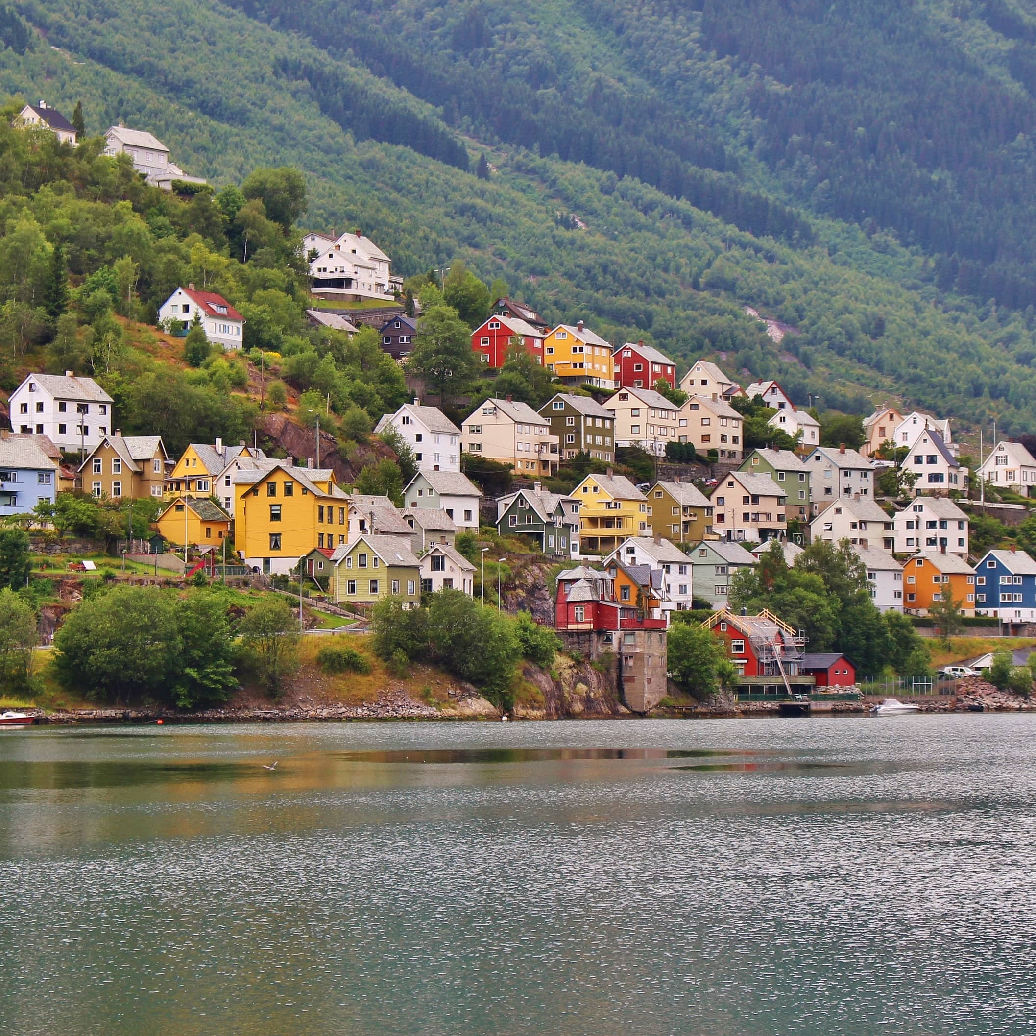 A view of colorful wooden houses in yellow, red, blue, green and white dotted by the water around Hardangerfjord