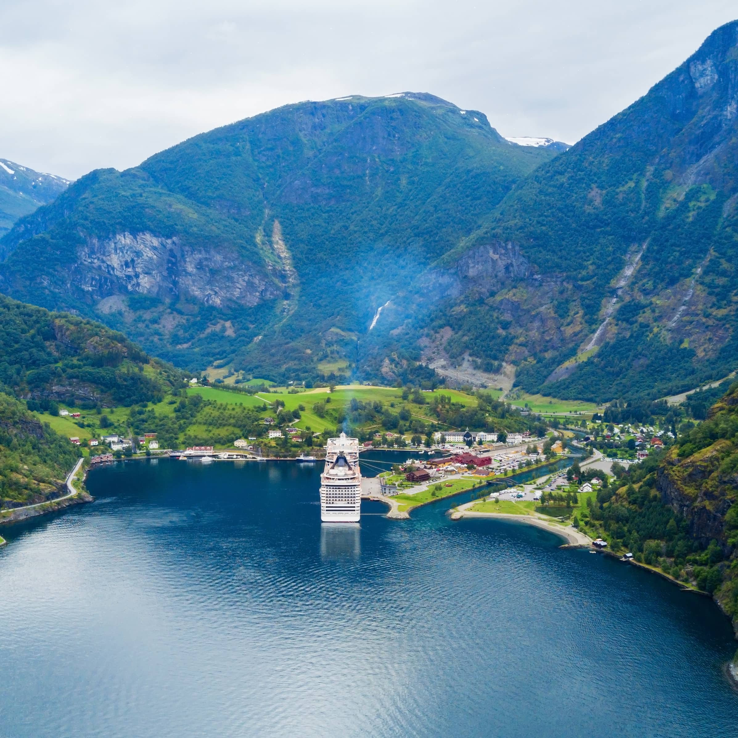 An aerial view of Flaam and the cruiseport with blue fjord water, the small village of Flaam surrounded by green gras fields and with majestic mountains right behind the village.
