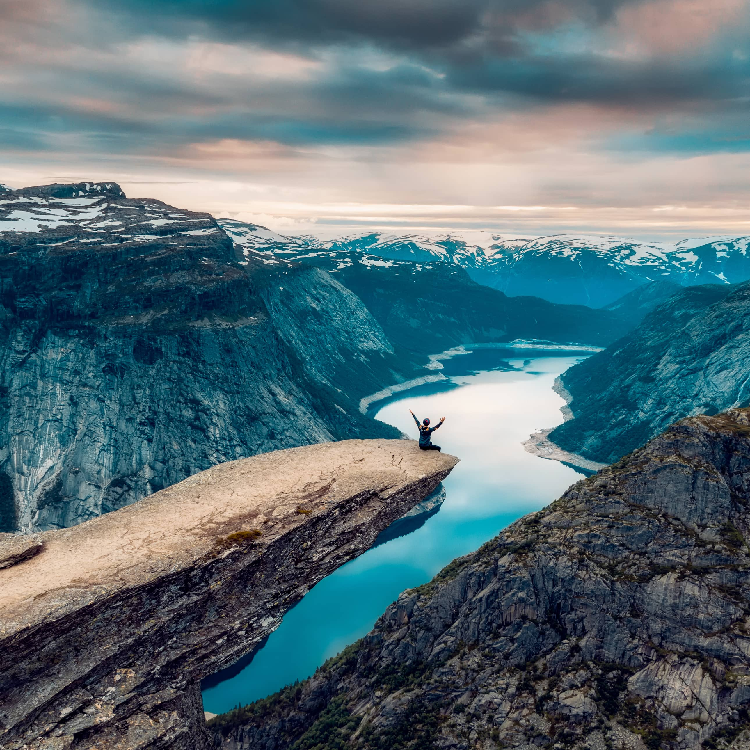 Person sitting at the edge of Trolltunga with arms out while overlooking Ringedalsvatnet and surrounding mountain landscape