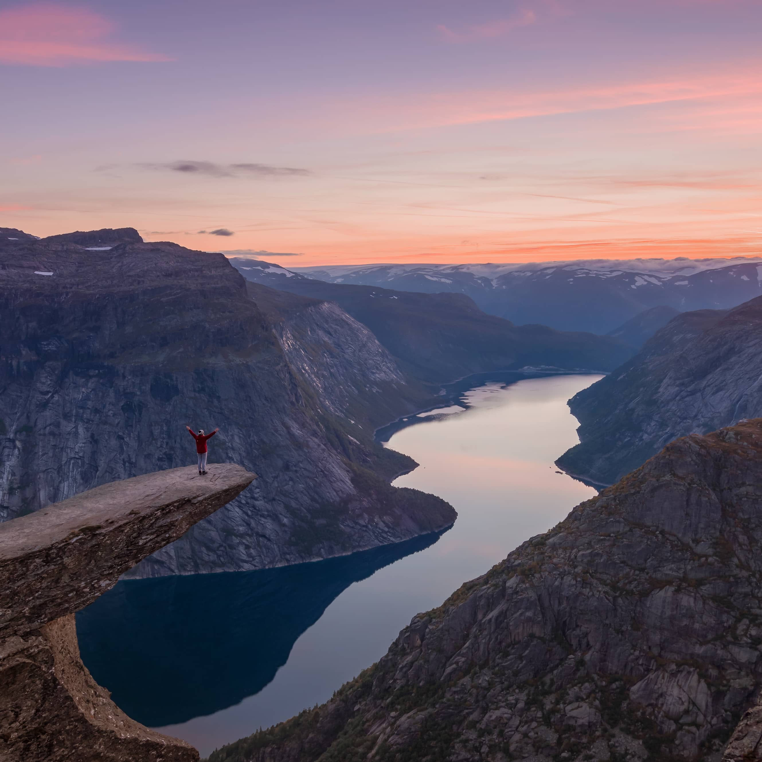 Person standing at Trolltunga overlooking the fjord and surrounding mountain landscape at sunset.