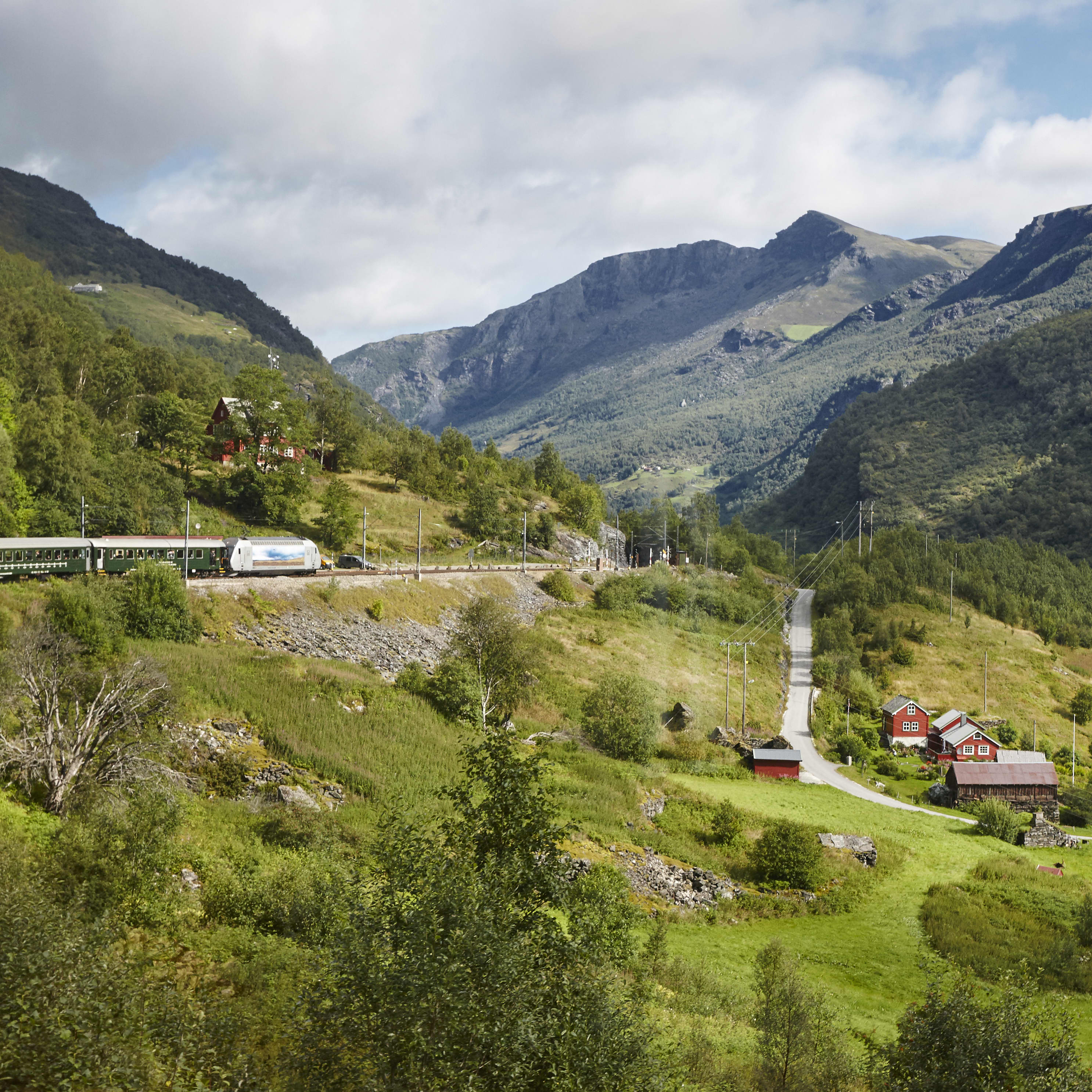 The train between Myrdal and Flaam is passing by green landscape with tall mountains and a small village with colorful red houses.