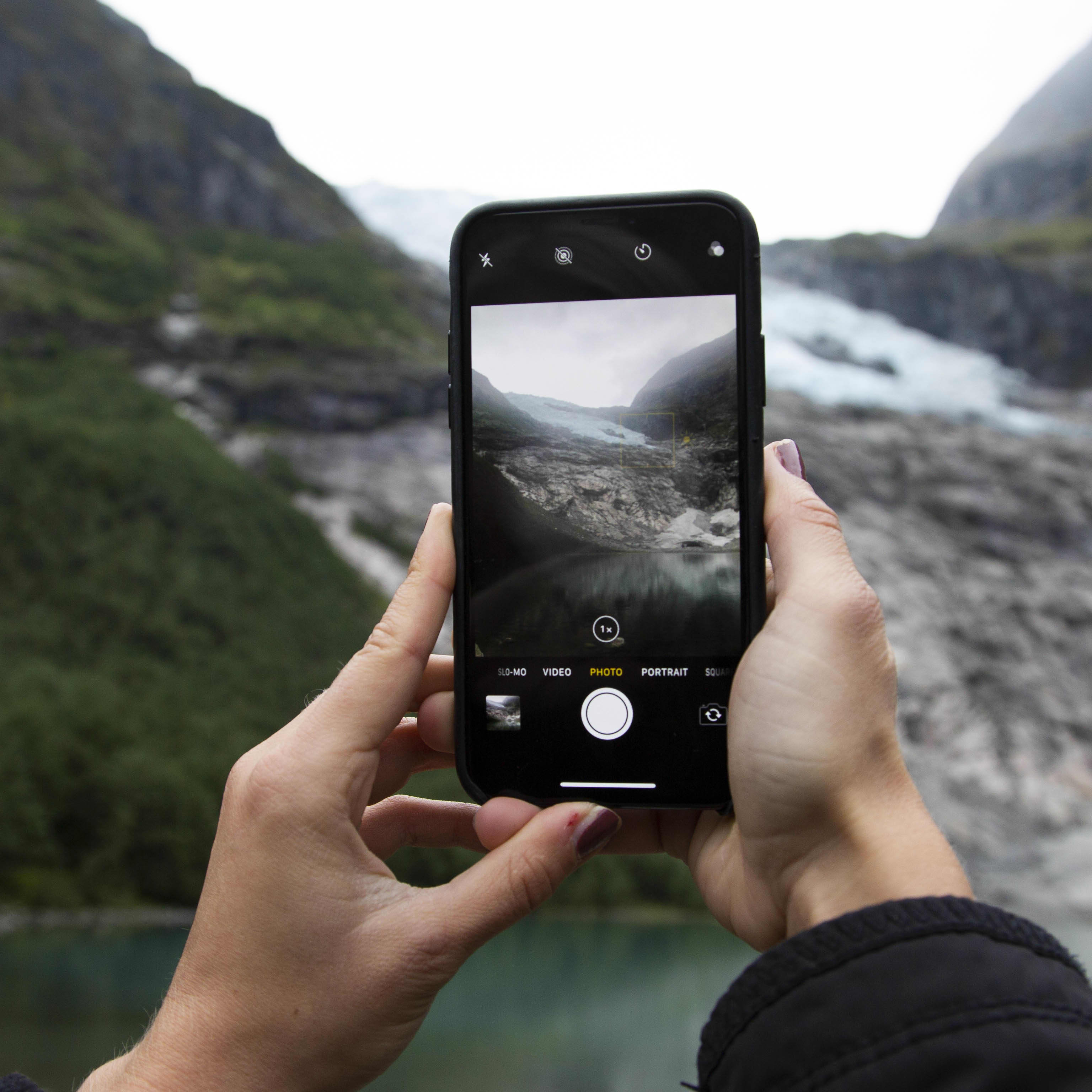 A picture of a black iPhone taking a picture of the small blue arm of Jostedalsbreen named Bøyabreen.