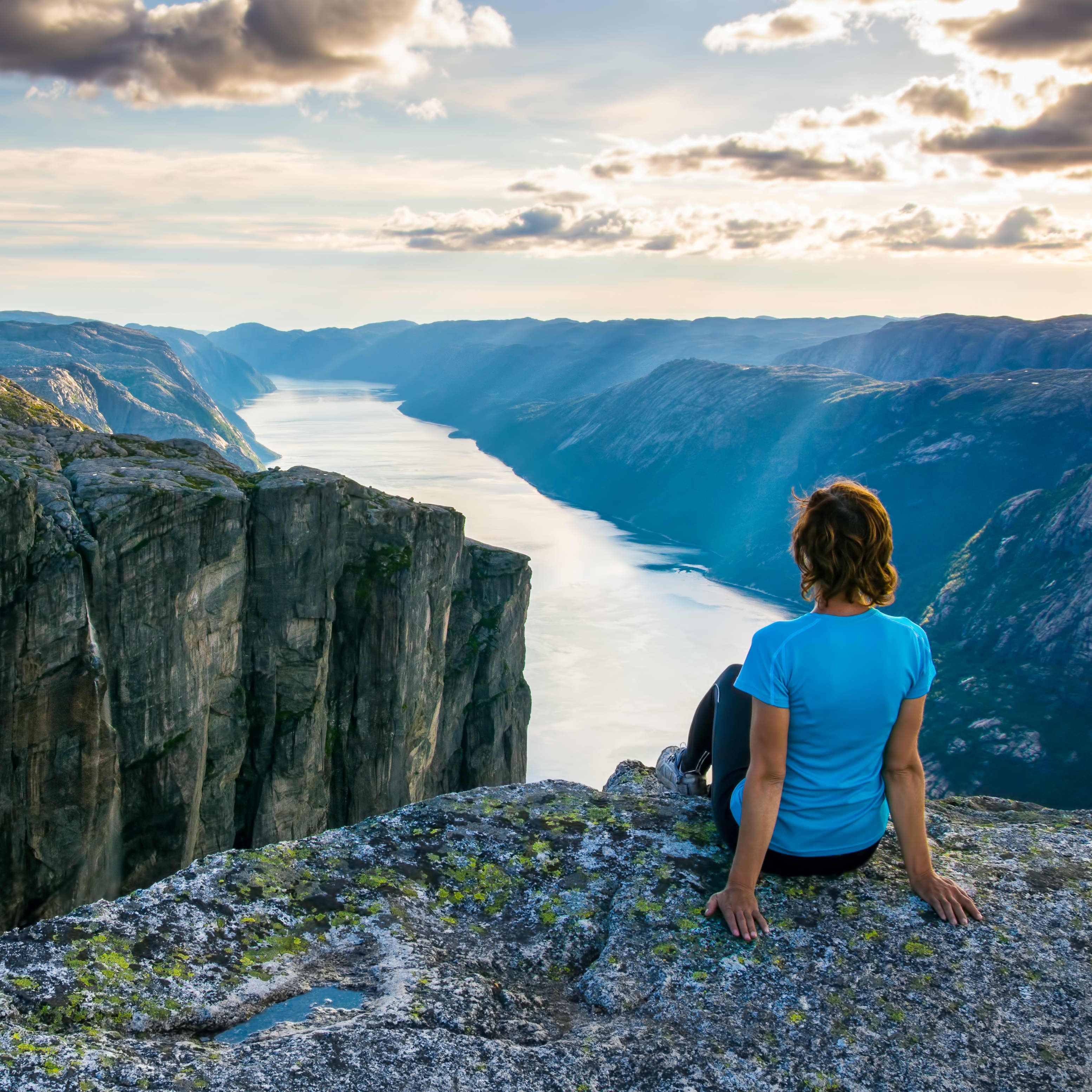 A woman is sitting on the edge of cliff on the way to boulder (Kjeragbolten) stuck in between the mountain crevices of Kjerag above a fjord, near Lysebotn, Norway. The feeling of complete freedom.
