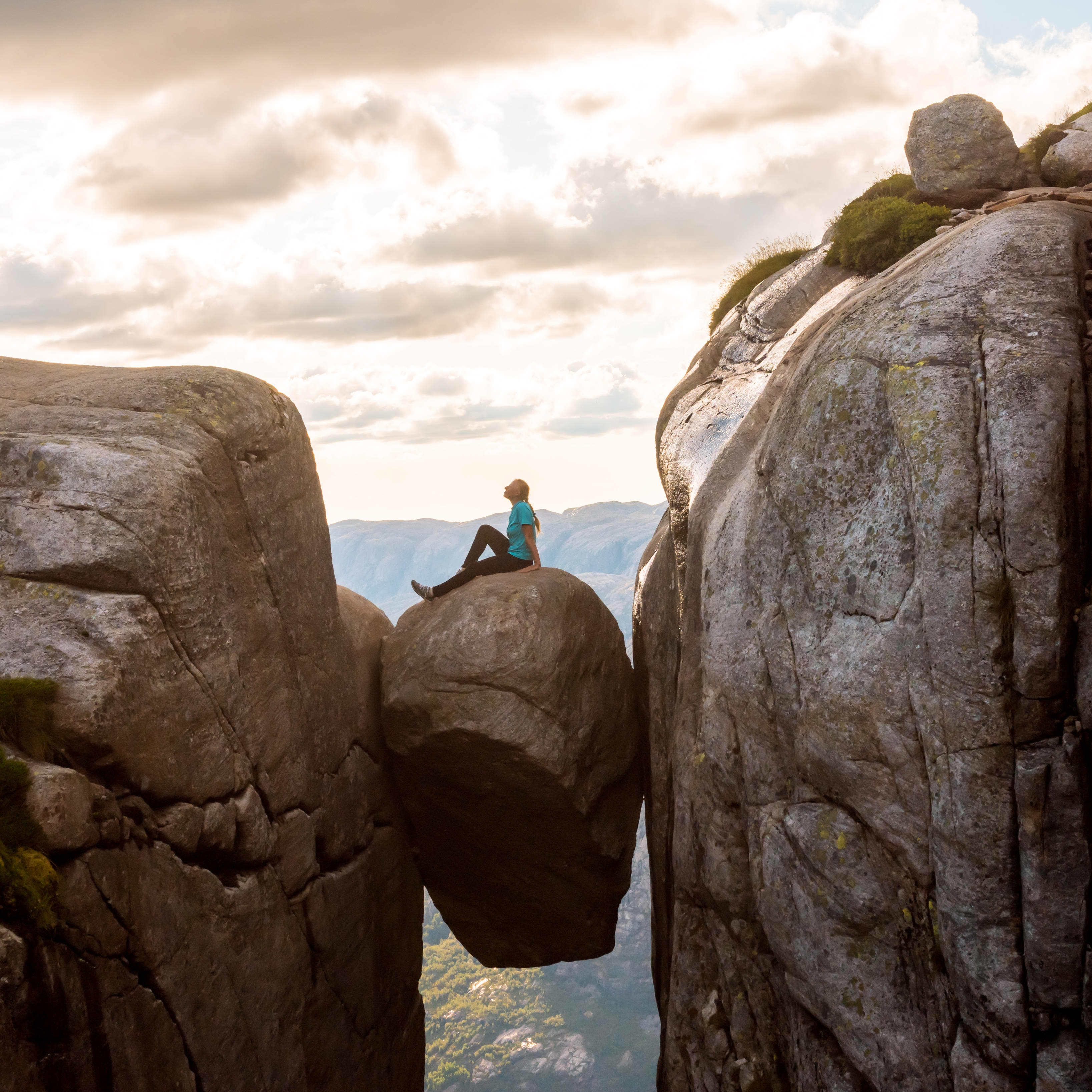 Woman on Kjeragbolten Travel in Norway Kjerag mountain in southwestern Norway