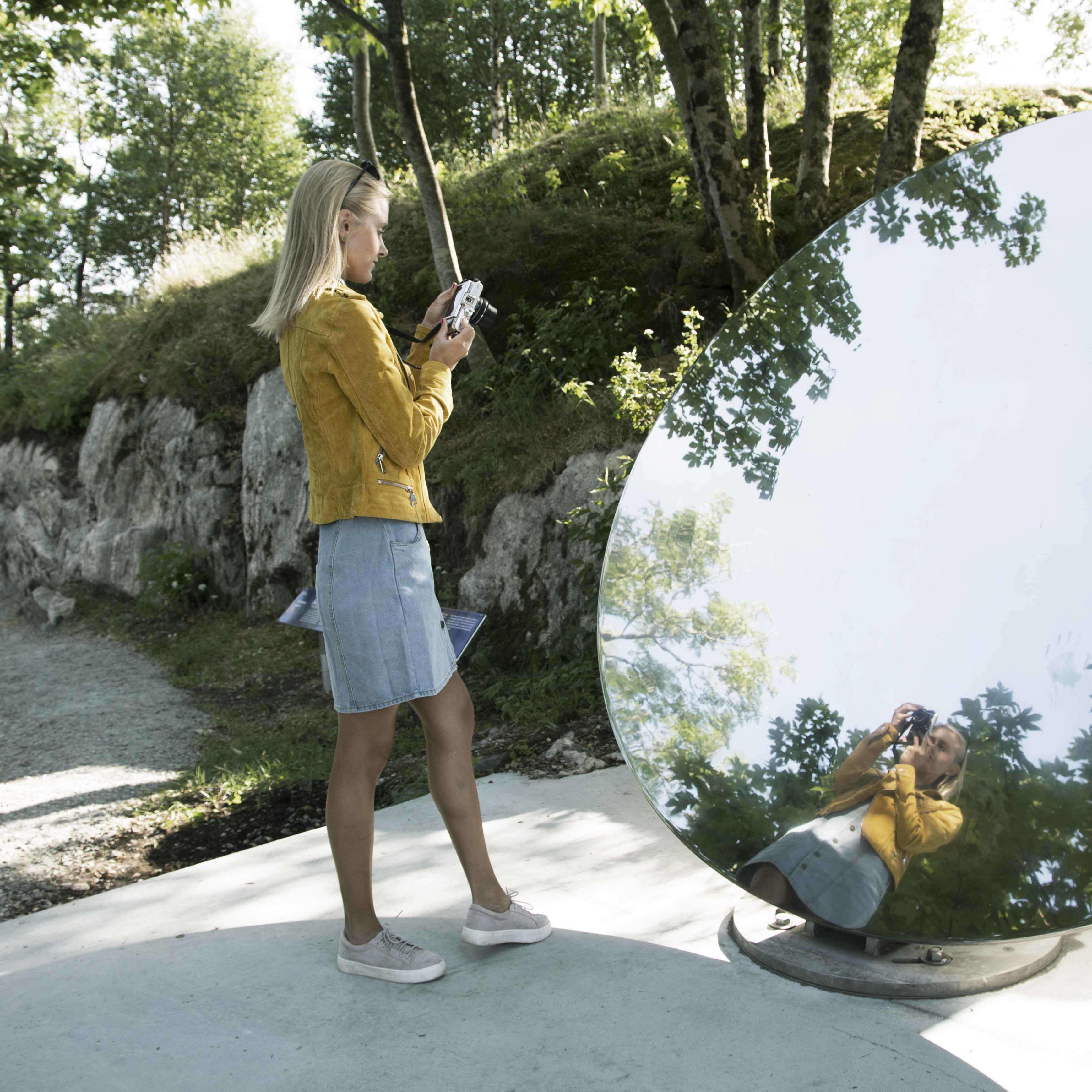 A girl looking into an outdoor mirror  reflecting herself in nature at Blue Garden in Skjerjehamn i Western Norway.