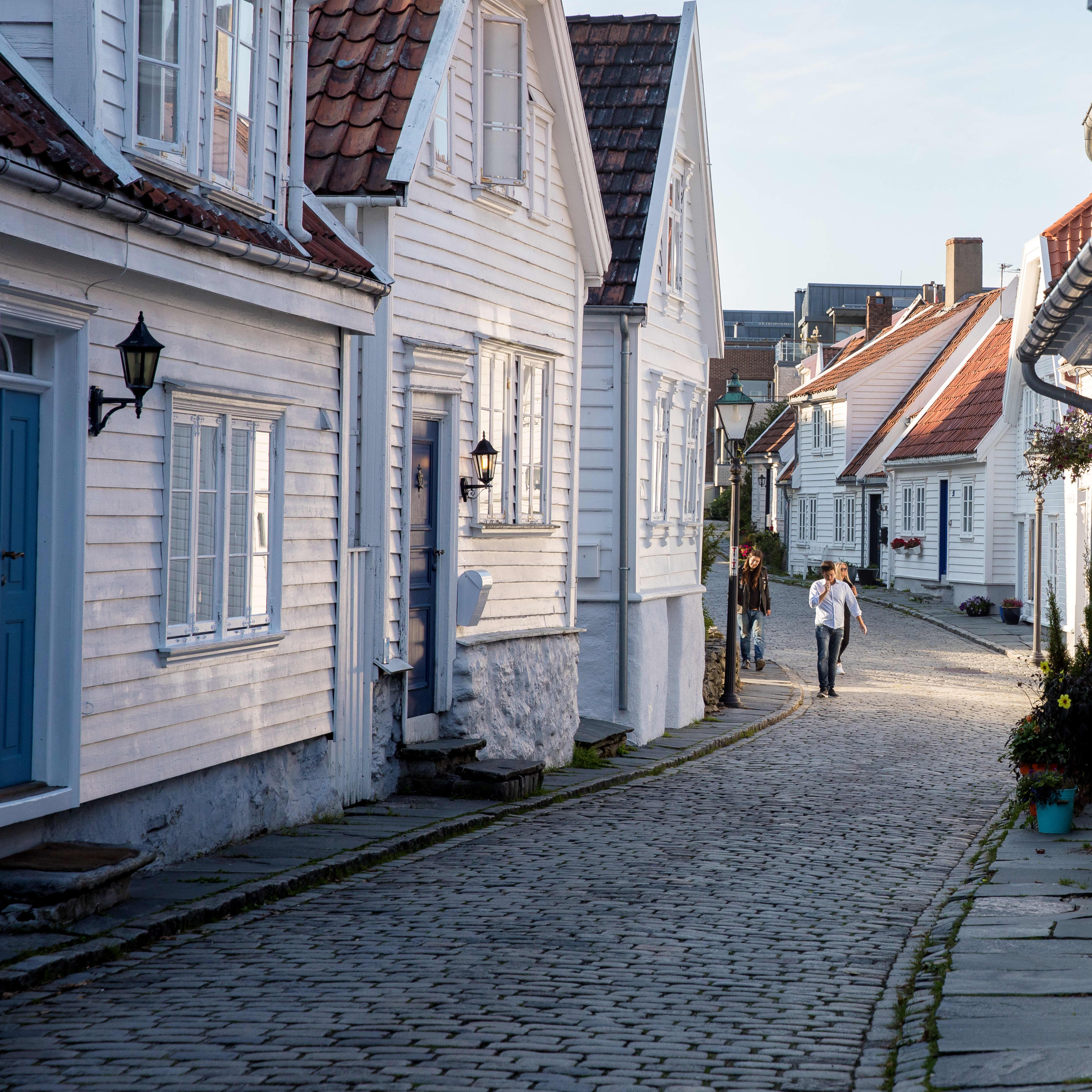 Cobble stone streets lined with white wooden houses with red roofs in Old Stavanger.