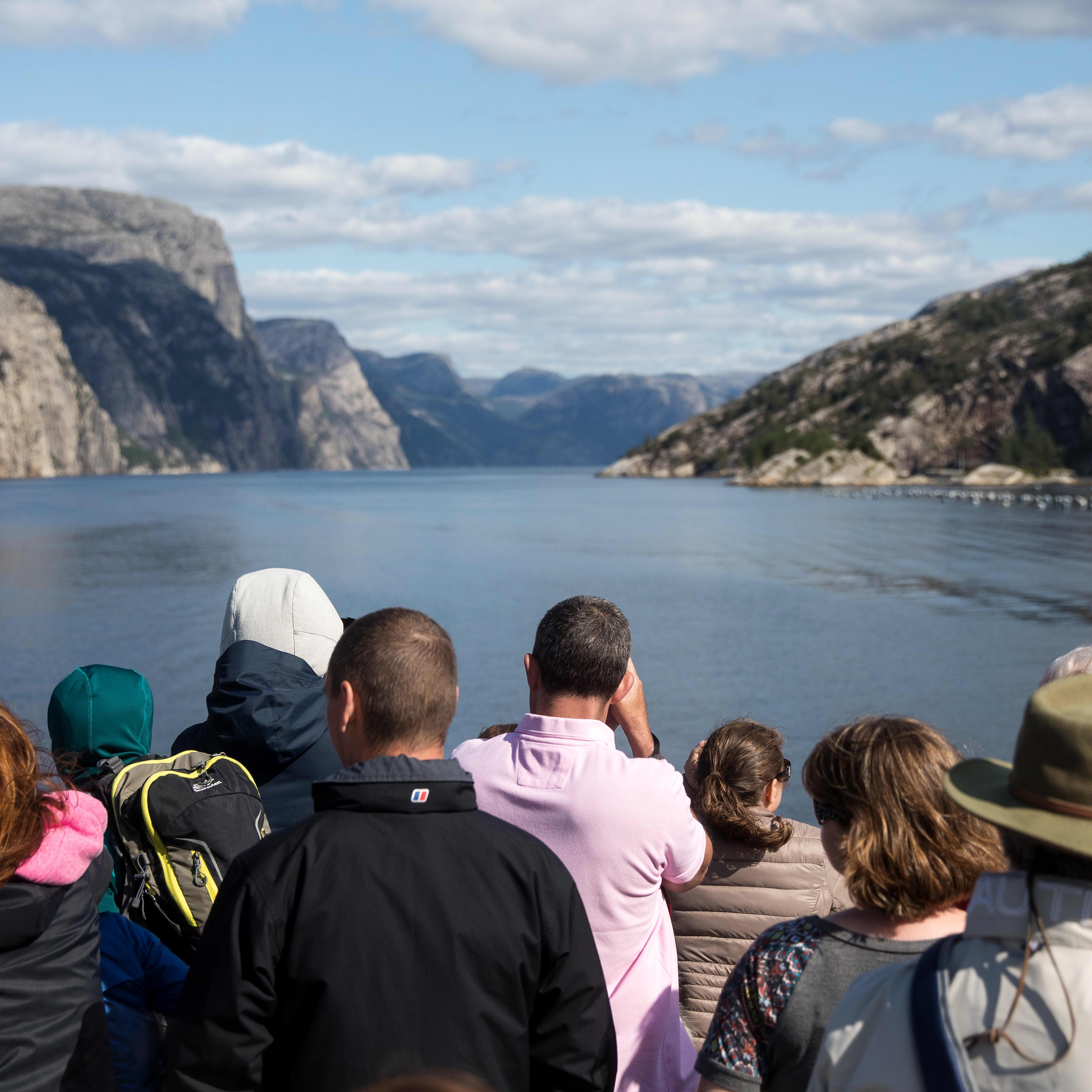 Busy tourists photographing the Lysefjord on a sunny day.