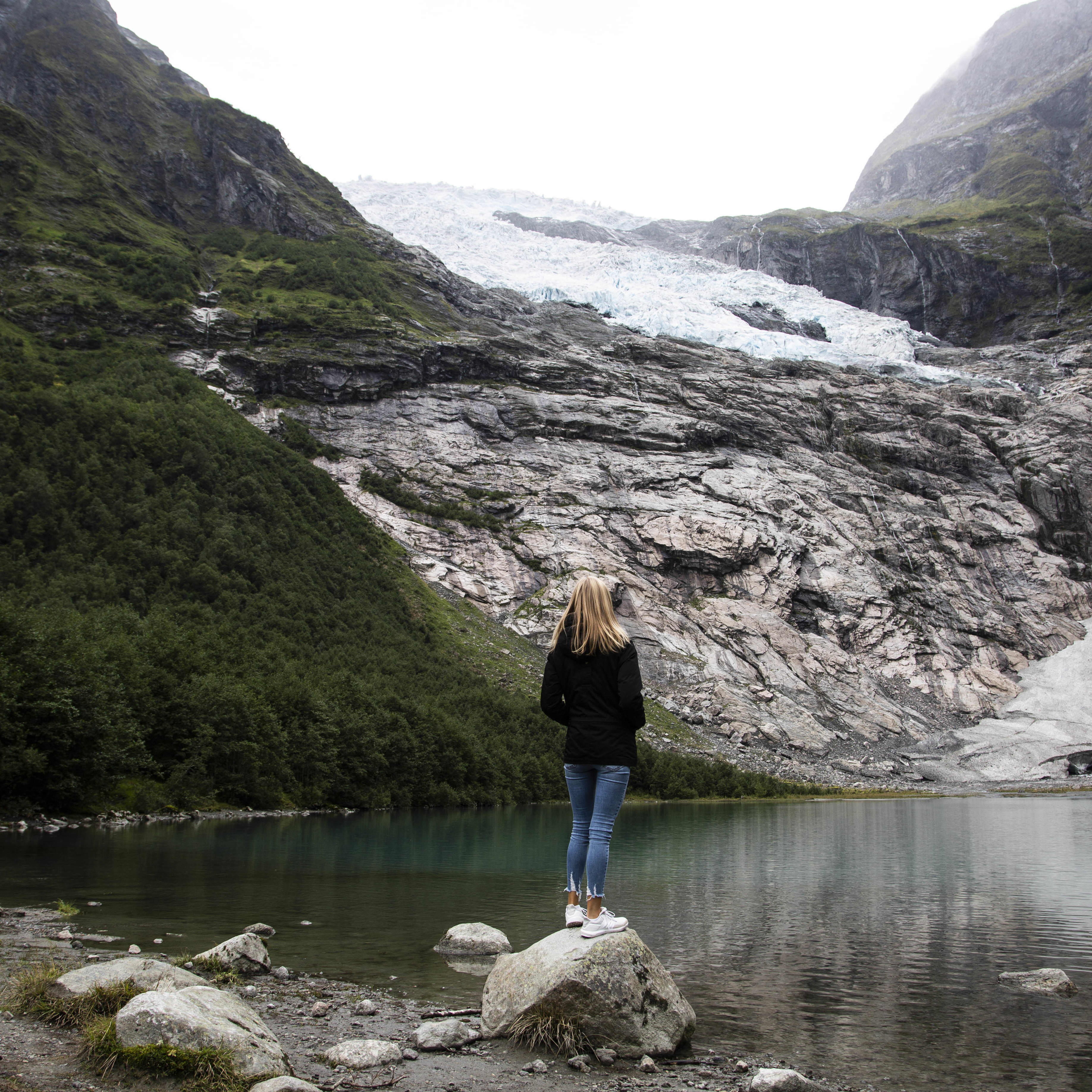 A girl with long blond hair and a black parkas standing on a small rock by the green water looking up at the small arm of Jostedalsbreen named Boyabreen.