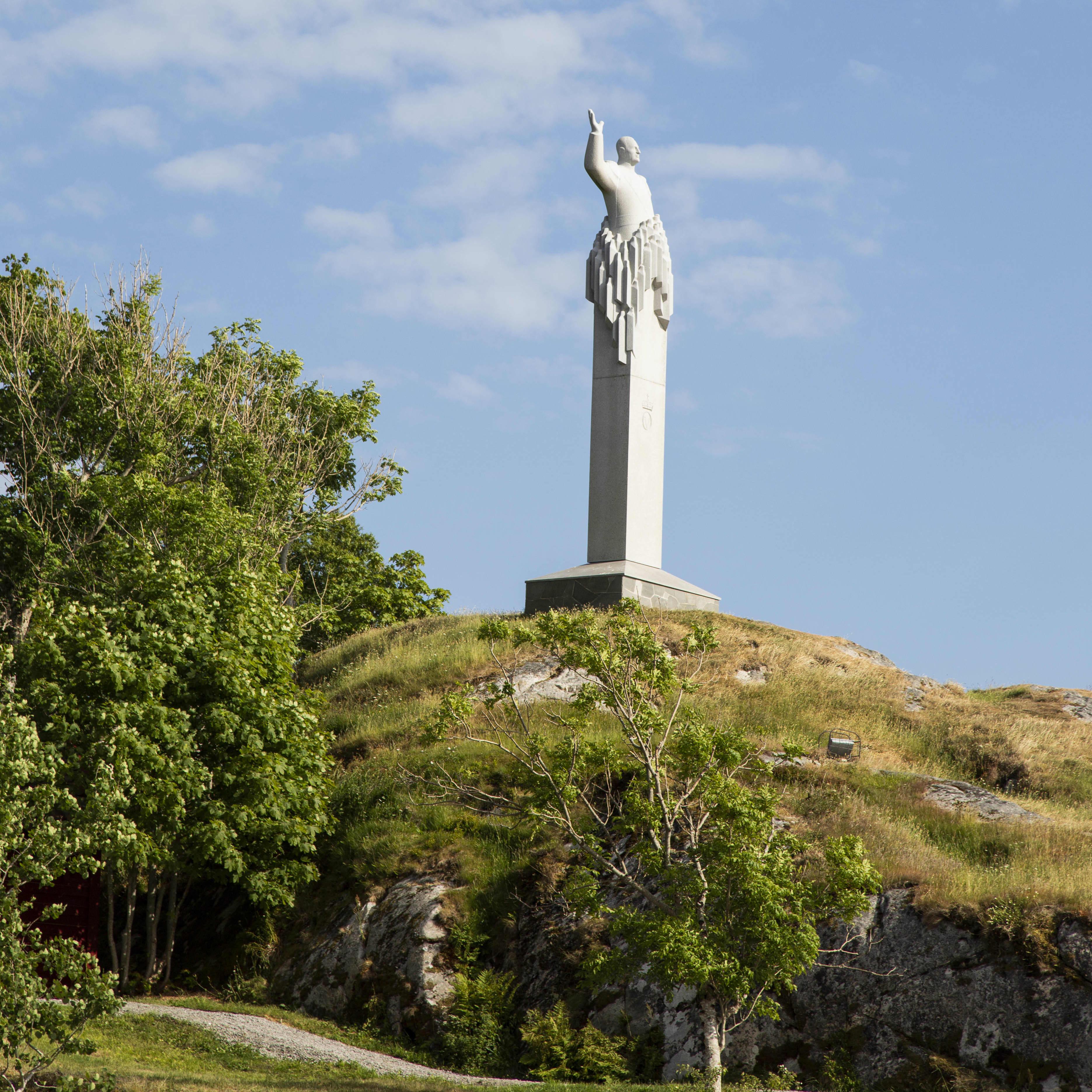 A statue of King Olav V standing on top of a hill in Skjerjehamn.