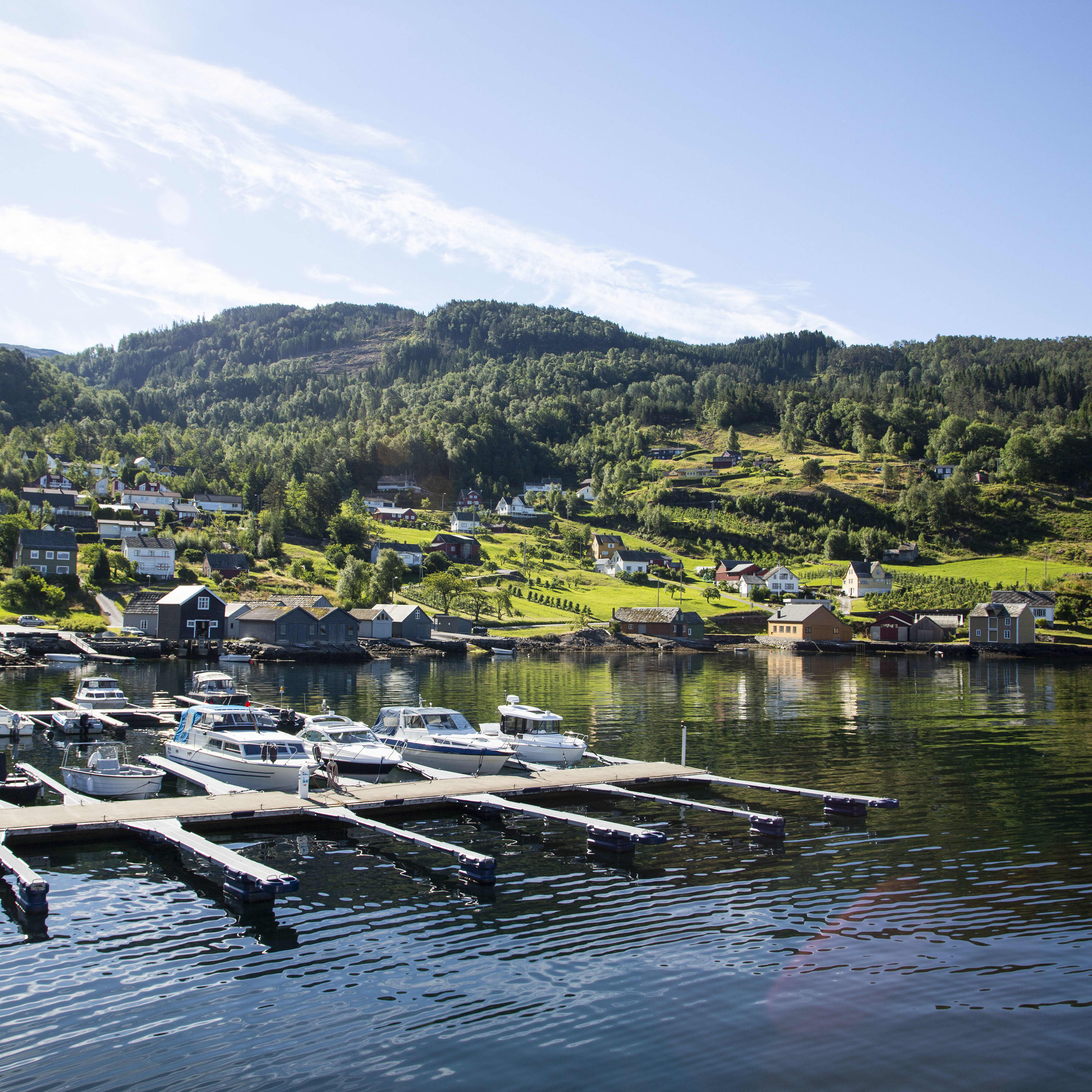 A view of the small town of Herand located in Hardanger from the boat deck sailing into to the port. The view covers a small boat harbour as well as green hills with wooden houses.