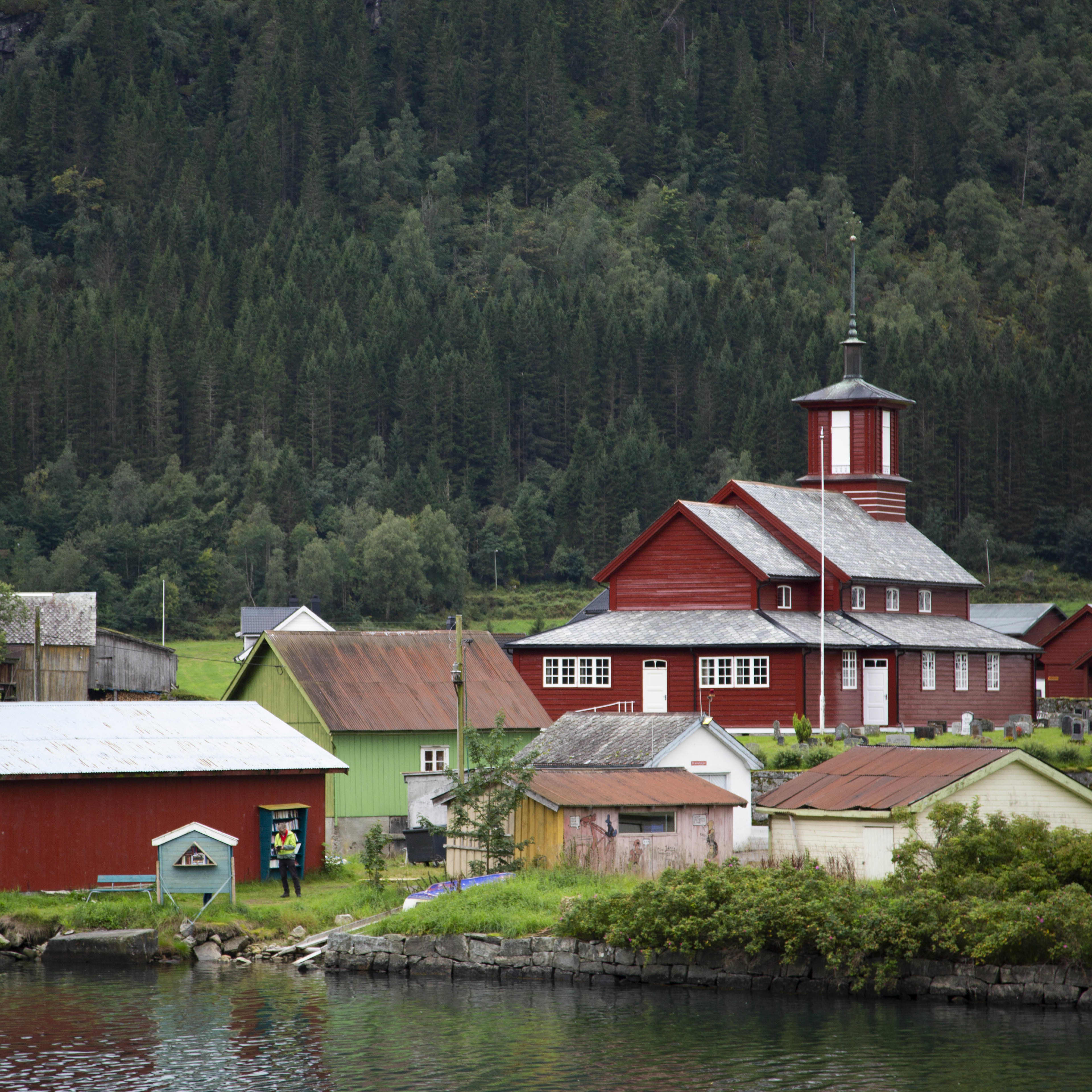 The small village of Fjærland seen from the water. The image portrays a red wooden church and some smaller houses in white, green and yellow surounding the church.