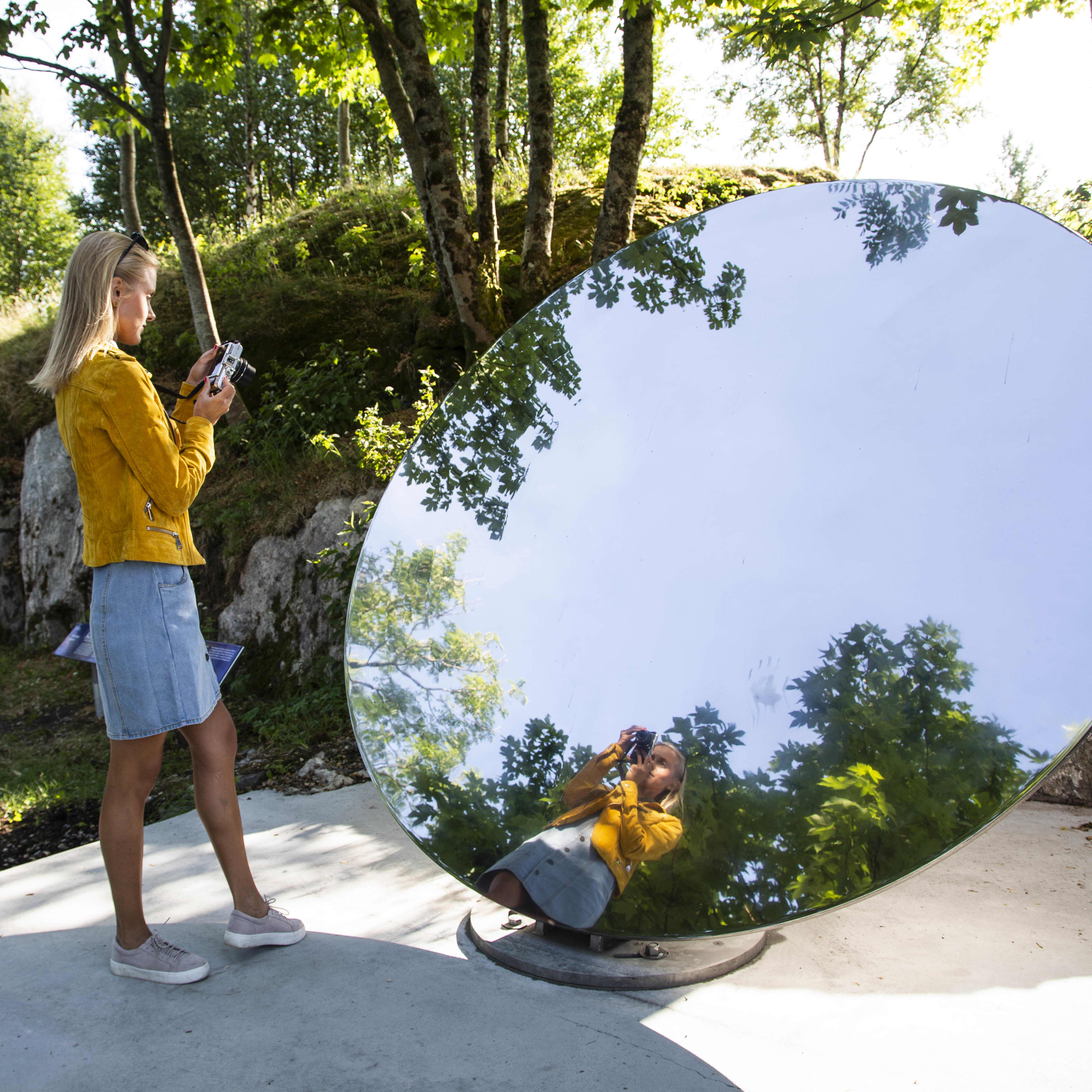 A woman taking a picture of herself in a large round outdoor mirror that reflects her and the green trees and blue sky that surround her.
