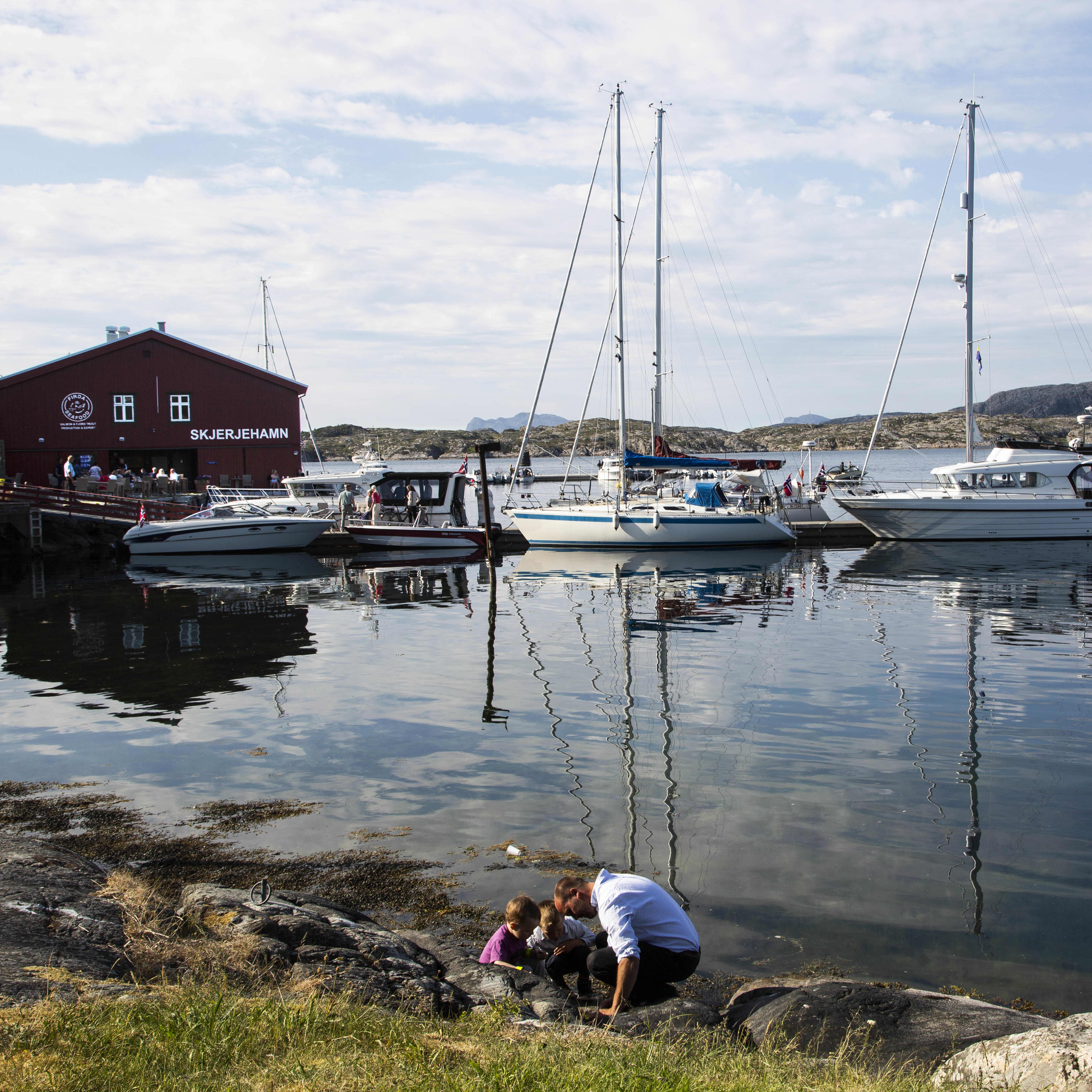 A man playing with two children by the water. In the background you see houses and boat mirrored in the water.