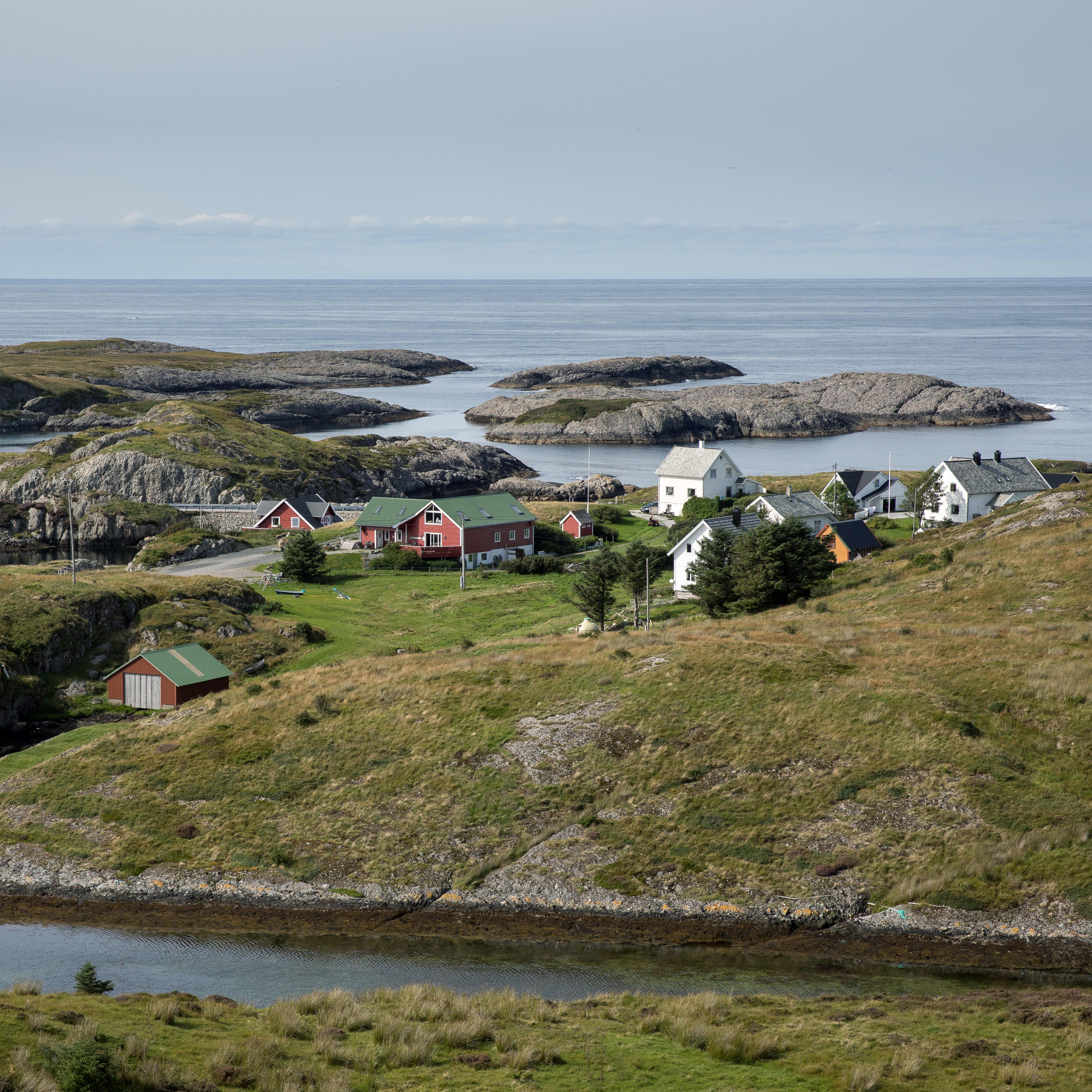 A photo of Bulandet with some private red, white and yellow homes located between small islands and inlets.