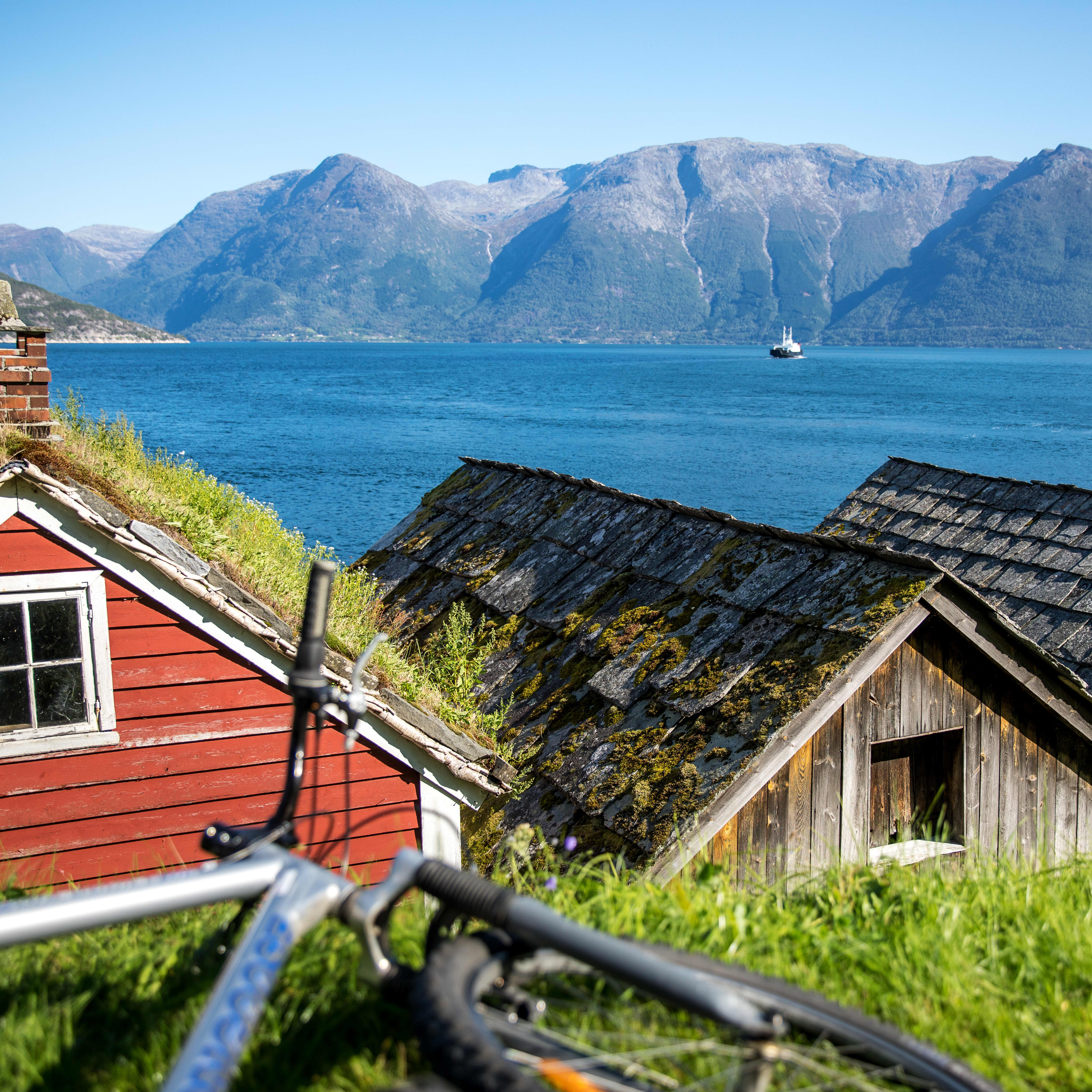 The Hardangerfjord with brown and red wooden houses in the foreground.