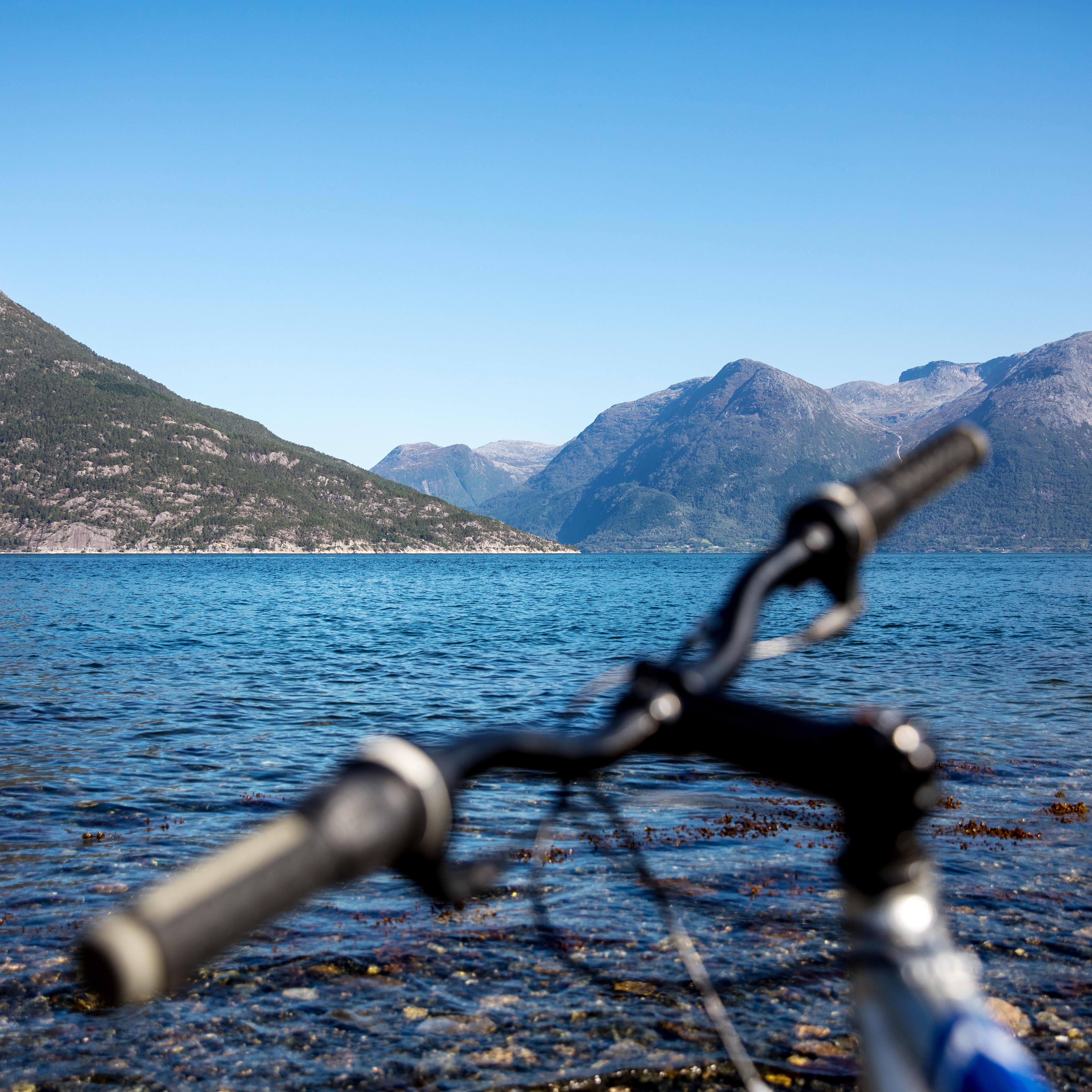 The steering while of a bike facing the blue waters of the Hardangerfjord backed up by rock mountains.