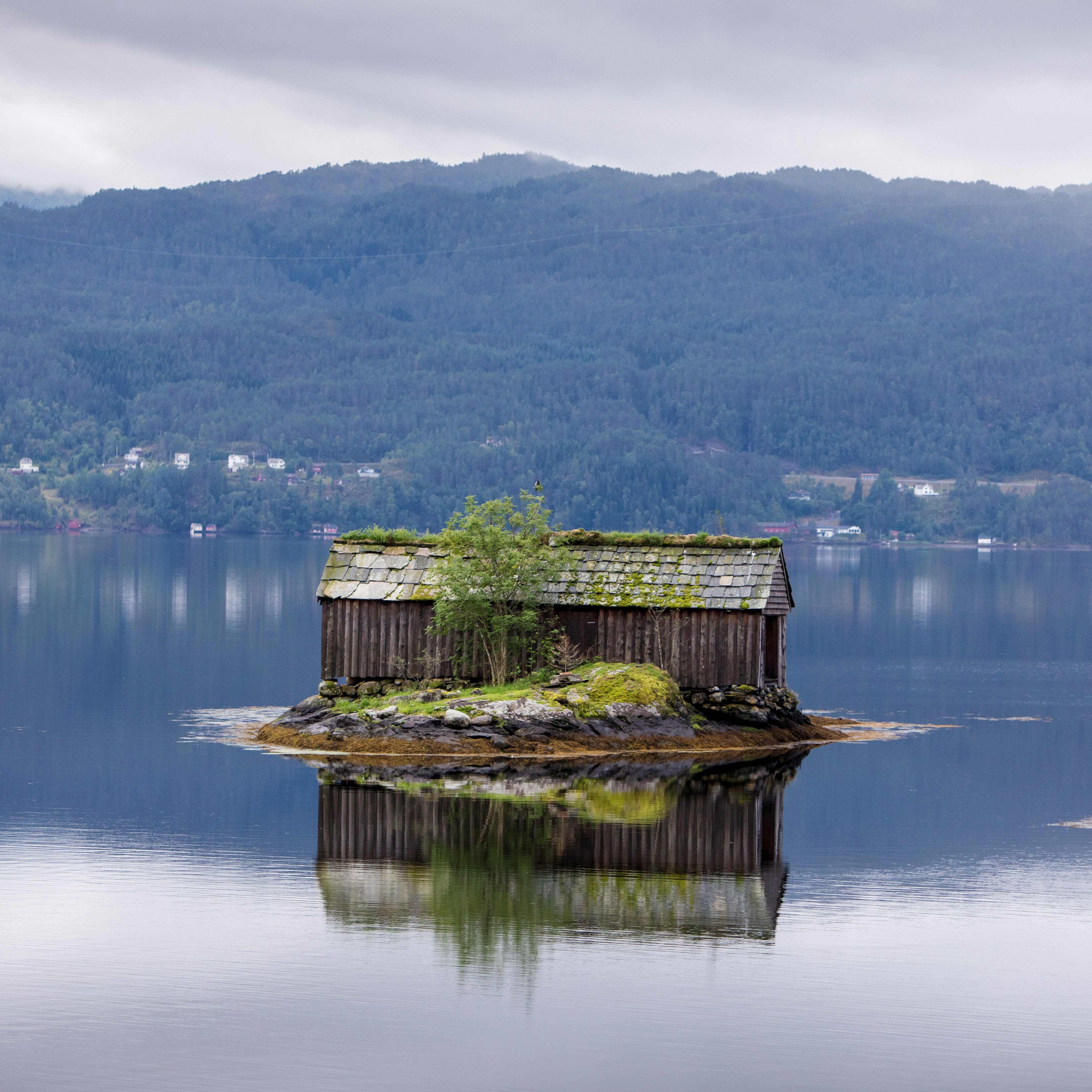 A small brown wood house sitting on an island in the middle of the blue Hardangerfjord surrounded by water and with a small hillside in the background.