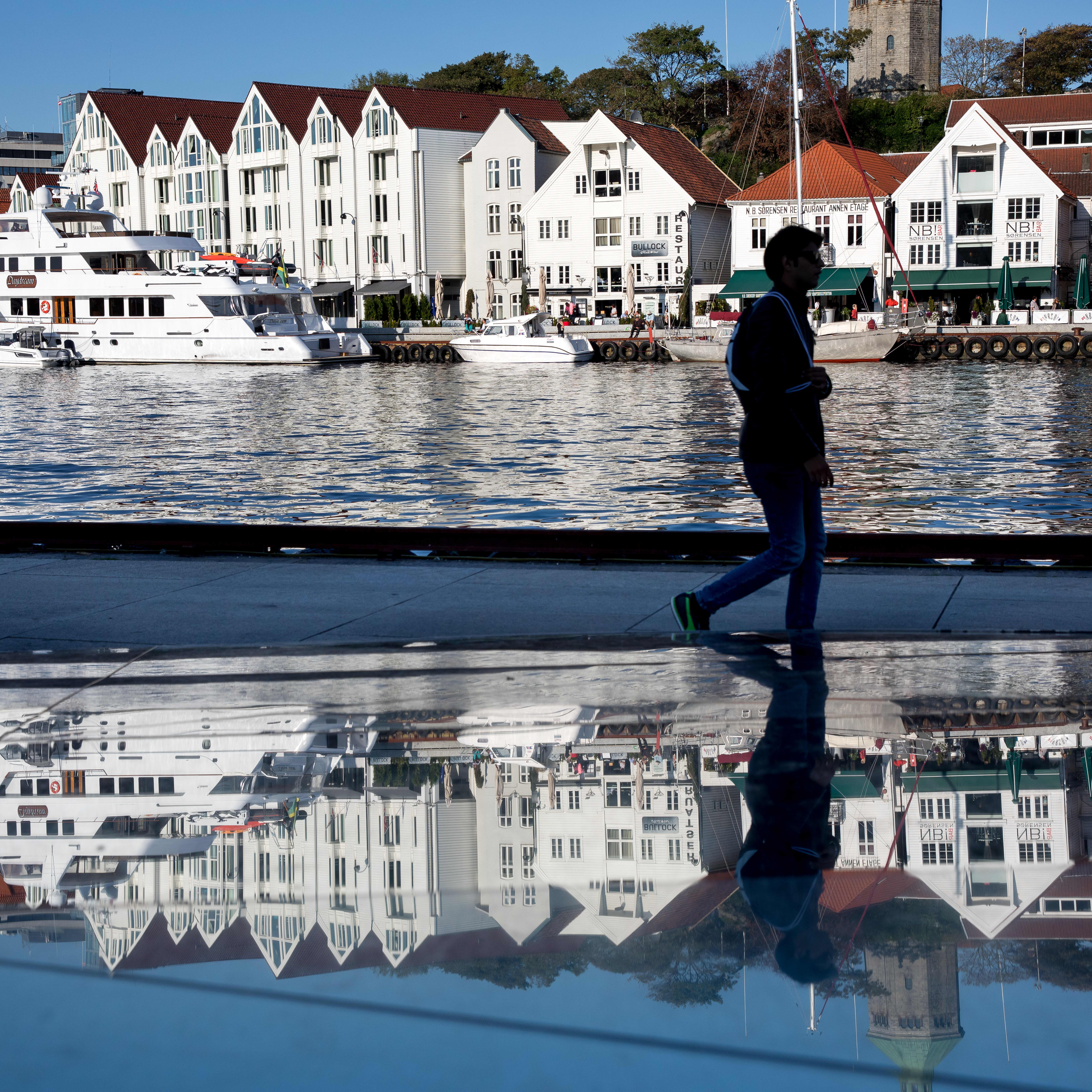 A reflection of down town Stavanger waterfront with the silhouette of a young man mirrored in a glas monument.