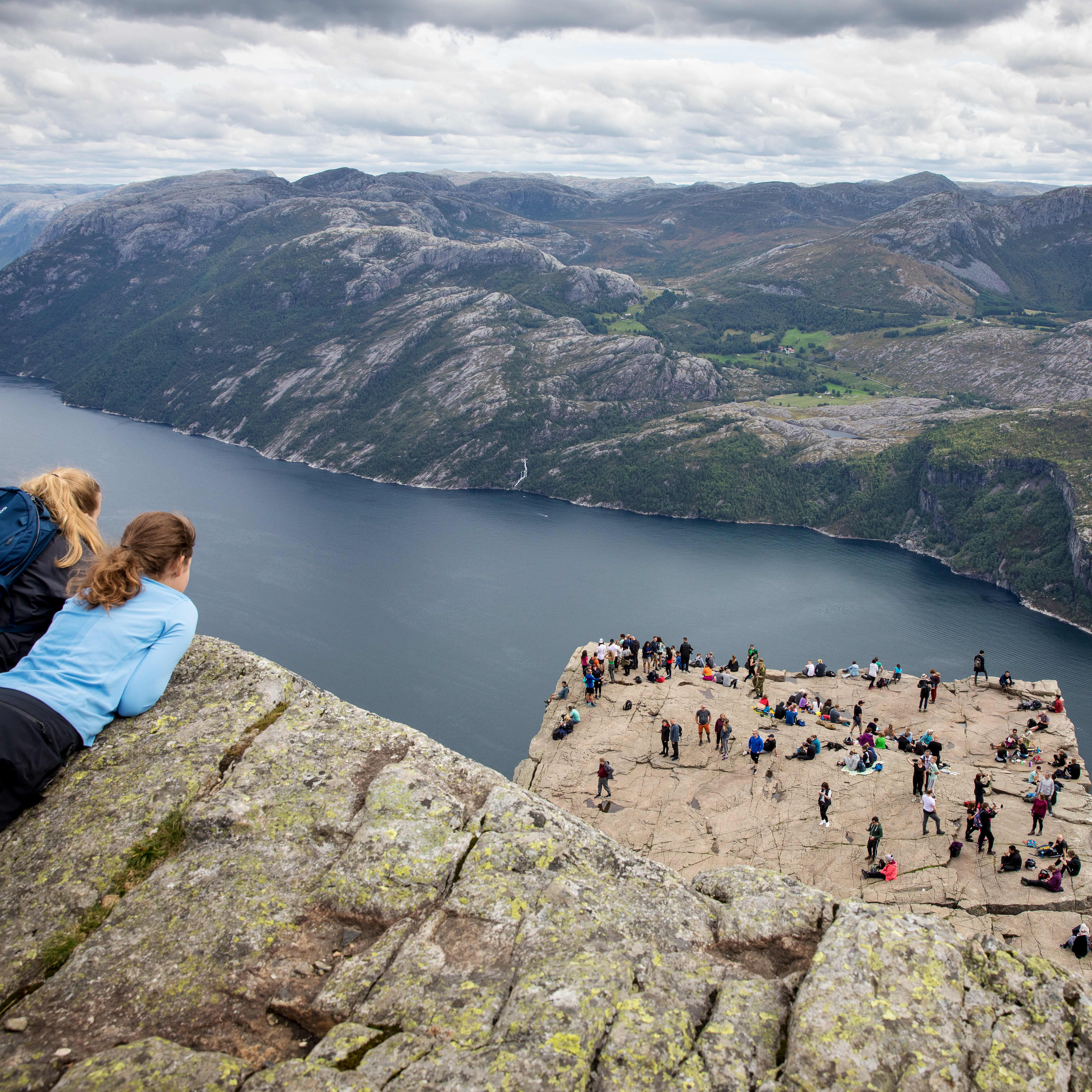 Two girls lying on a cliff above Preikestolen looking down at a large crowd of people that are walking on the rock itself. In the background you see Lysefjorden and the surrounding rock landscape.