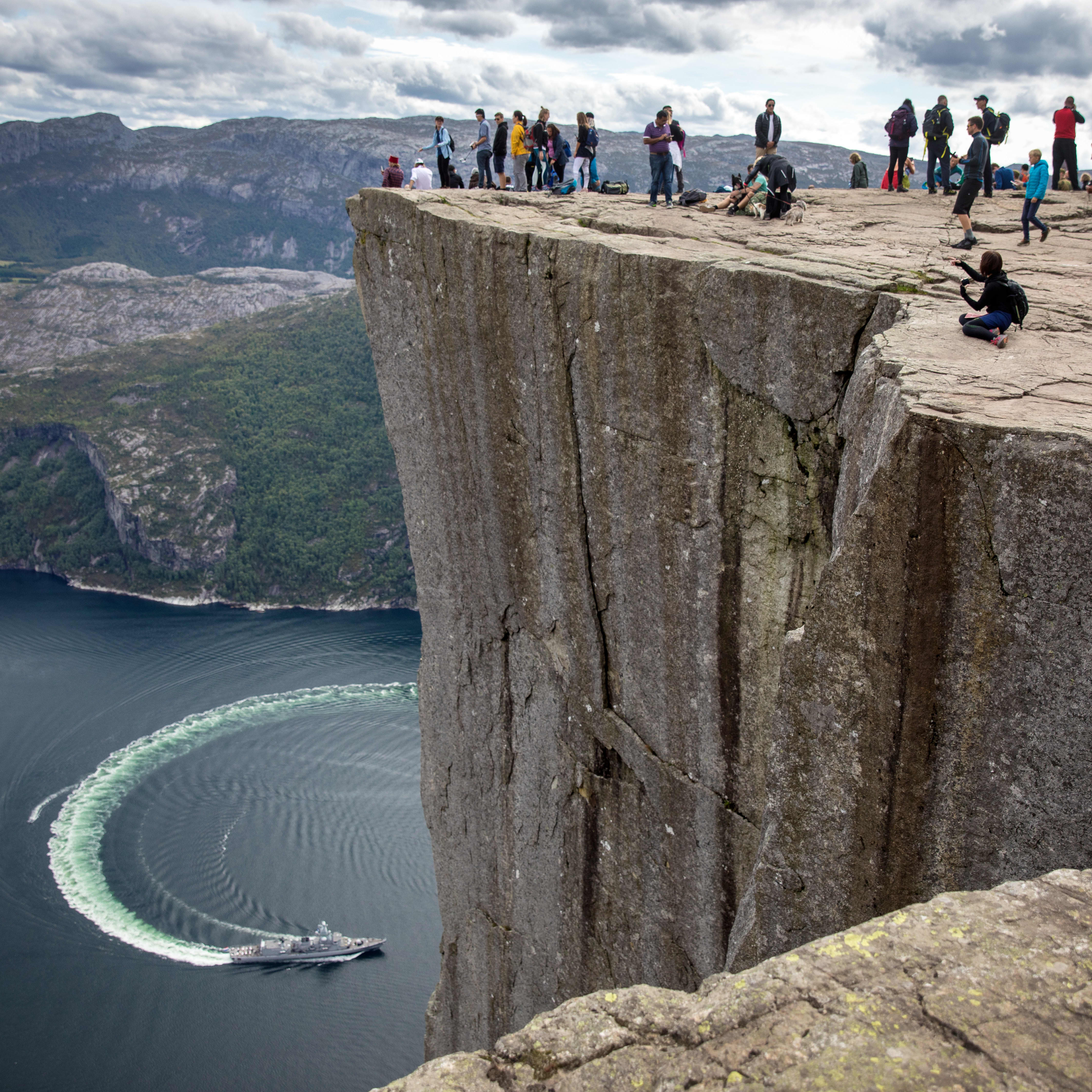 A view of Preikestolen from the side. You see the rock formation towering over the Lysefjord. In the fjord a boat is making a circular turn. On top of the rock many people are busy taking pictures and looking at the view.