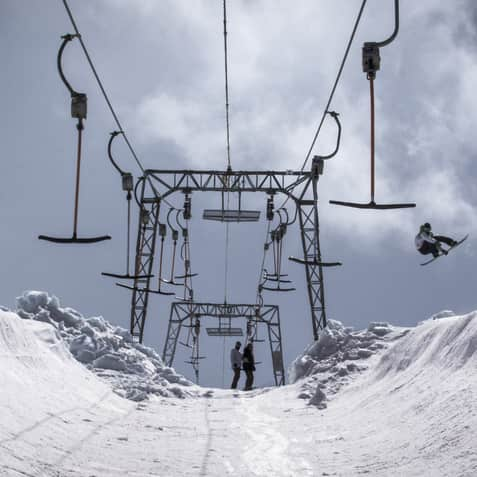 Snowboarder jumping under a T-bar at Folgefonna, Norway.
