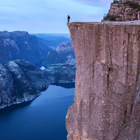 A hiker standing at the edge of the Pulpit Rock looking down at Lysefjorden