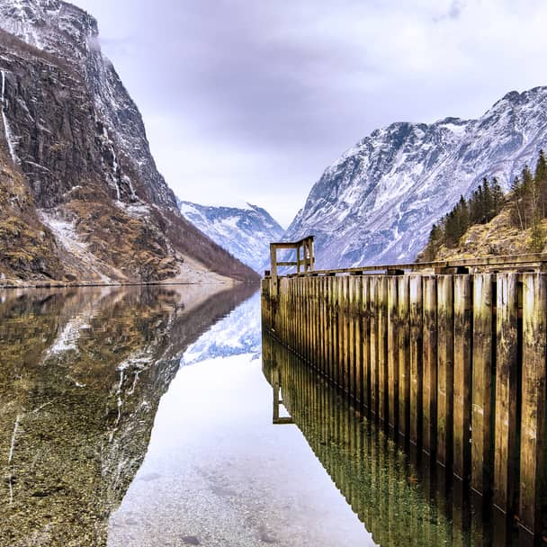 The majestic mountains surrounding Sognefjorden is reflected in the water