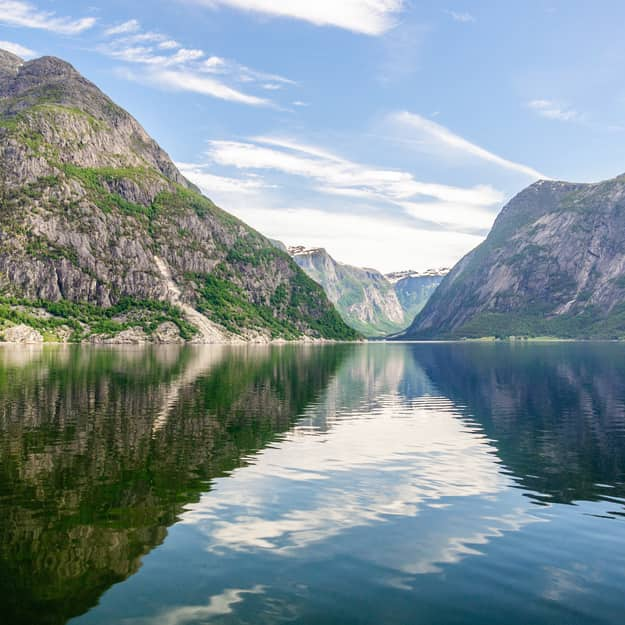 Reflection of clouds in the water and wonderful natural landscape view on the mountain peaks with green slopes, Norway, Hardangerfjord