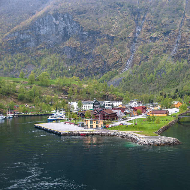 A view of Flaam seen from the ocean with the village in the foreground backed up by mountains in the background.