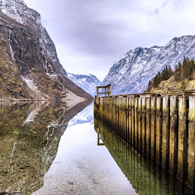 Tha majestic mountains surrounding Sognefjorden is reflected in the water
