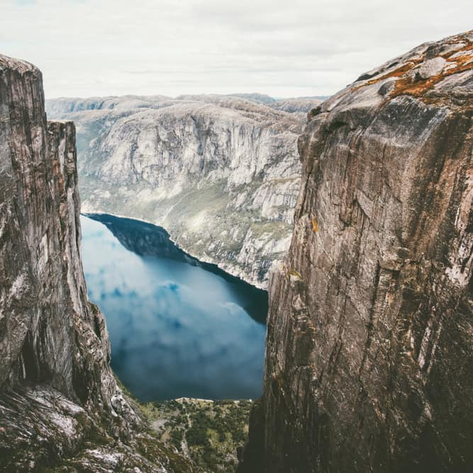 A view of the Lysefjord and its blue waters seen from the Kjerag boulder wedged between two steep rock cliffs.