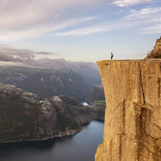 Person standing on the edge of the pulpit rock also know as Preikestolen