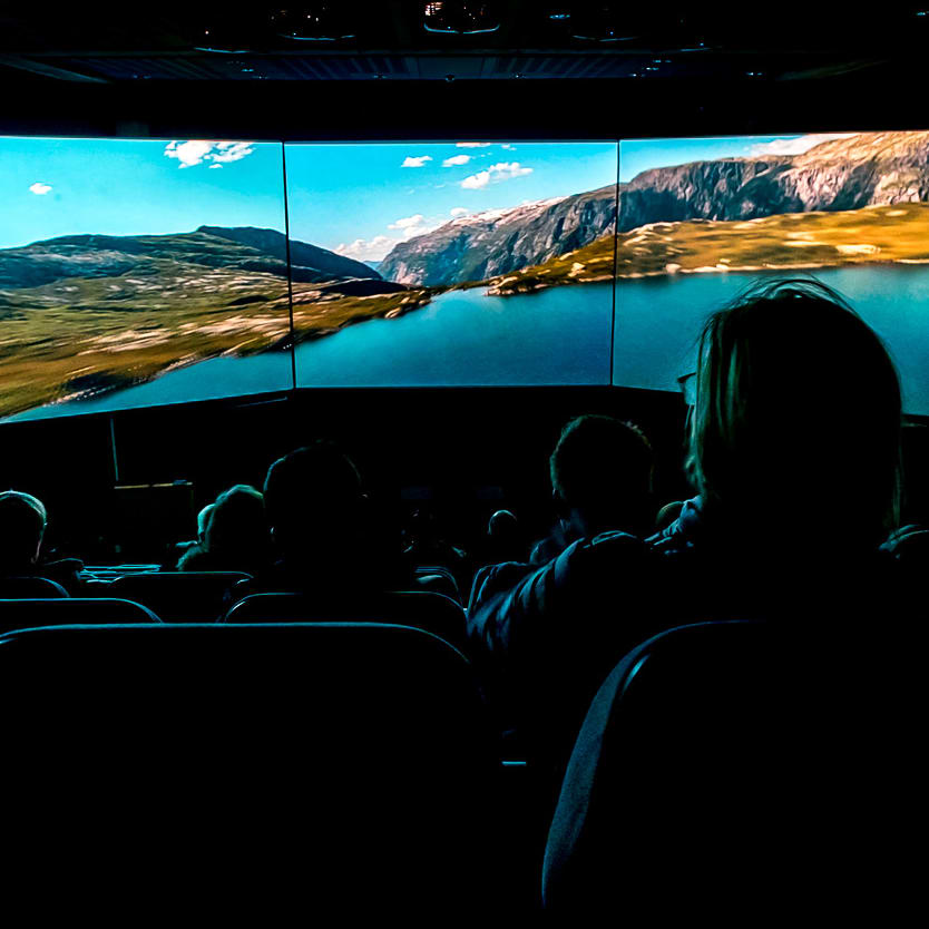 An audience sitting in chairs watching a panorama video at Hardangerfjord Nature Centre.