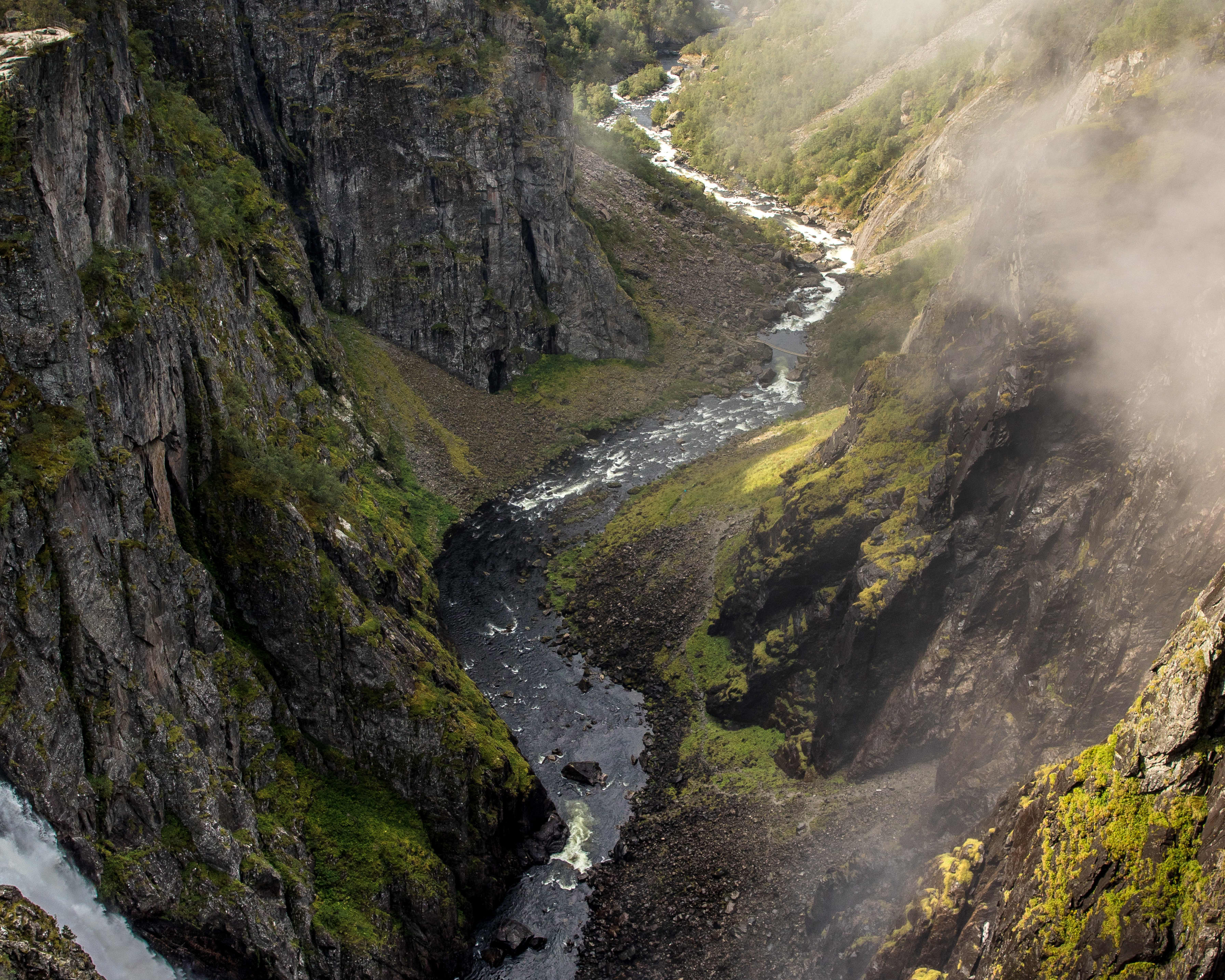 An aerial view of Vøringsfossen located in the mountainside. On the left you have the waterfall pooring water into the valley, and in you can see the streams and rivers that carry the water on in the valley between the mountain cliffs.