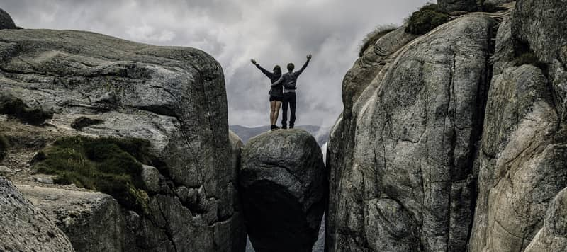 A couple standing on the edge of  the Kjerag bolt stuck in between the mountain crevices of Kjerag above the Lysefjord in Rogaland, Norway