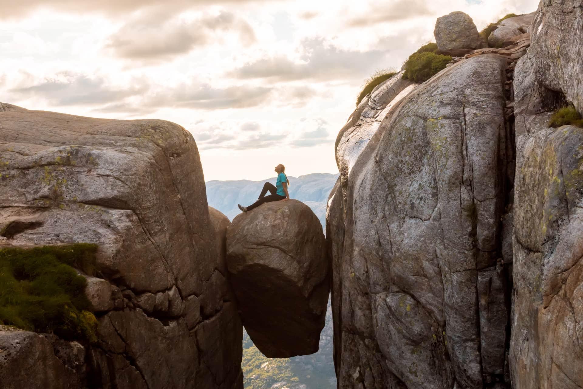 Woman on Kjeragbolten Travel in Norway Kjerag mountain in southwestern Norway