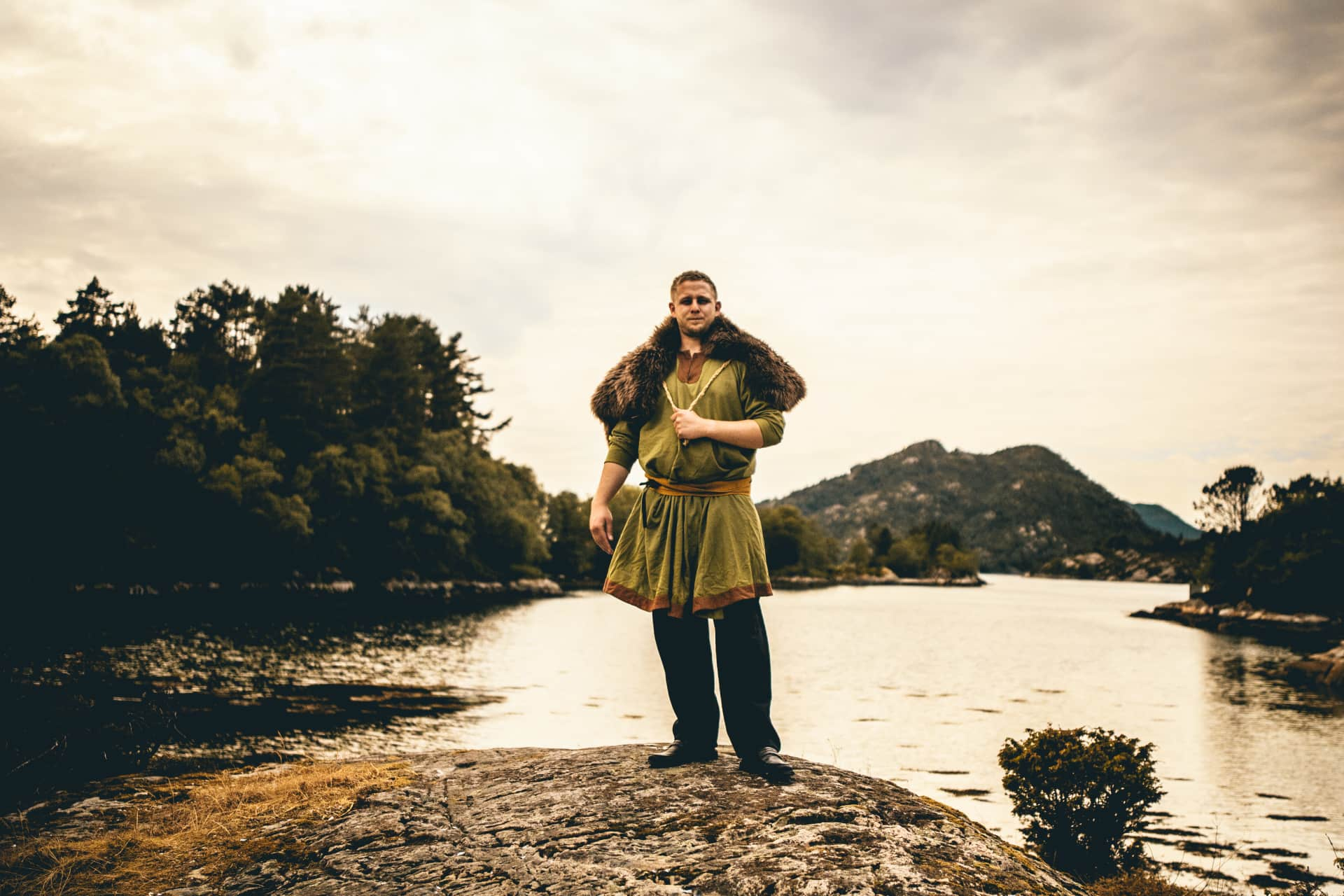 A viking dressed man standing at Gulating with the ocean as a backdrop.