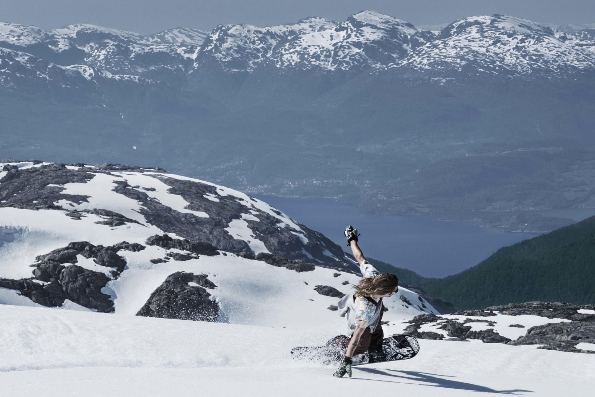 A person snowboarding on the folgefonna glacier in t-shirt with the Hardangerfjord visible in the horizon.