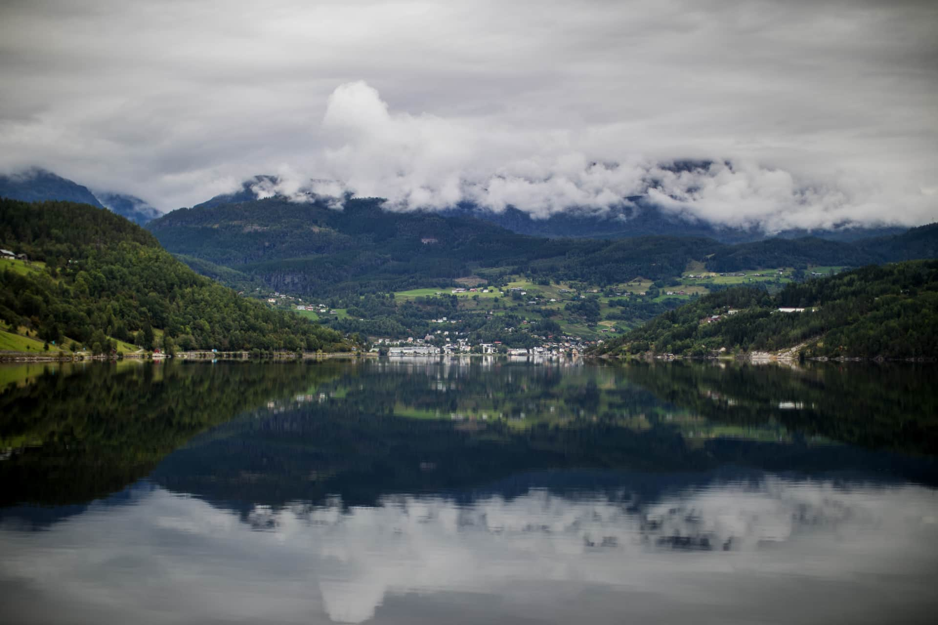 A water reflection of a cloudy landscape in the Hardangerfjord.