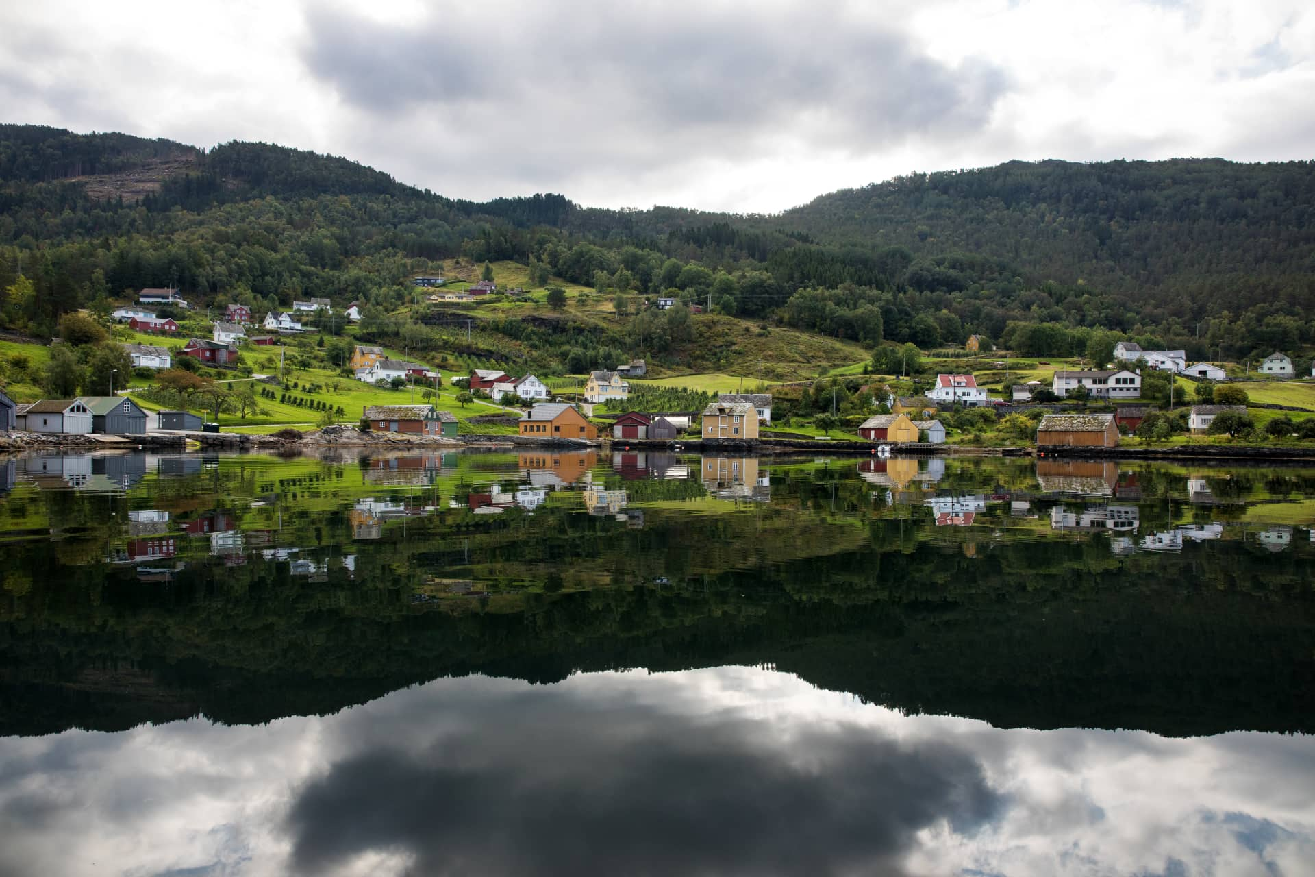 A reflection of a small village with houses in red, white, red and orange mirrored in the Hardangerfjord.