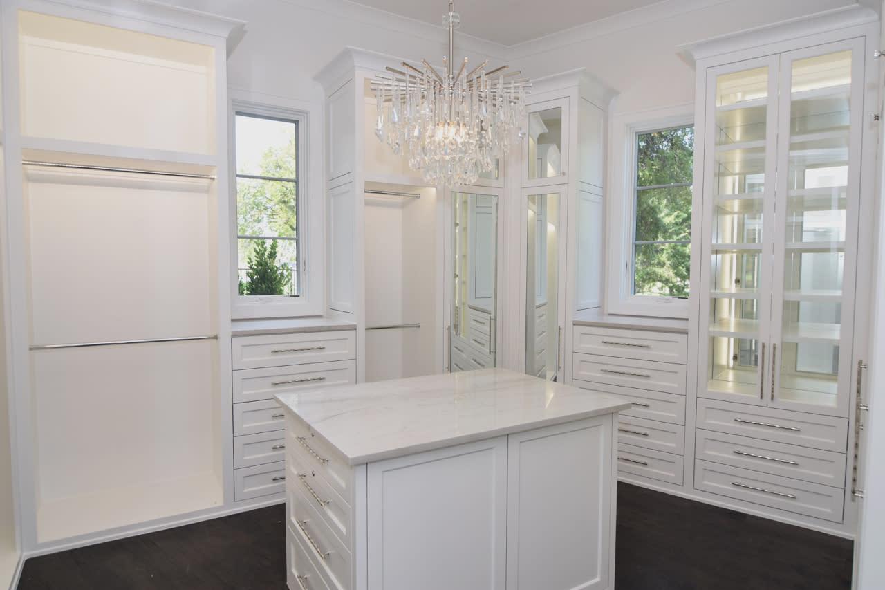 white wood master closet with mirrored doors