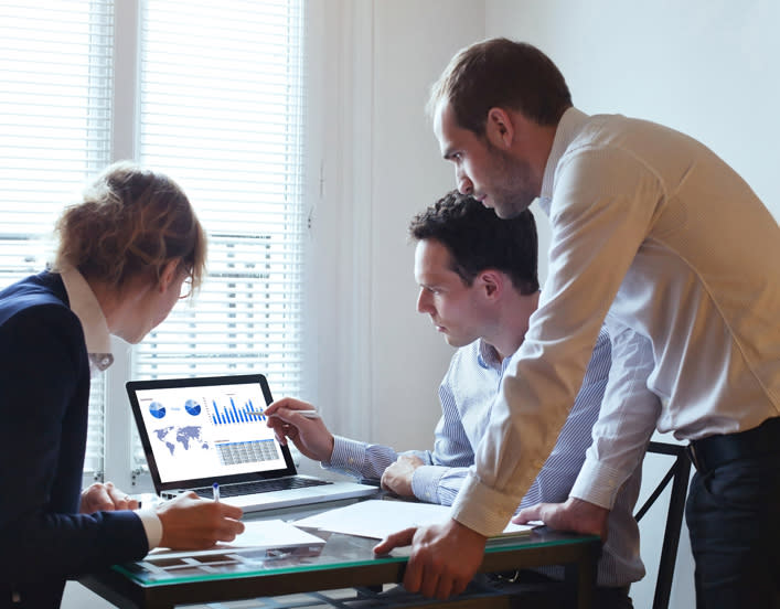 image contains 3 marketing specialist analyzing data on laptop