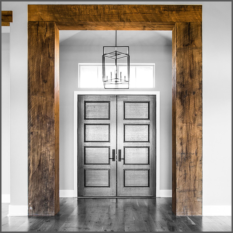 Rustic Oak wood beams frame a door threshold in a modern ranch home.