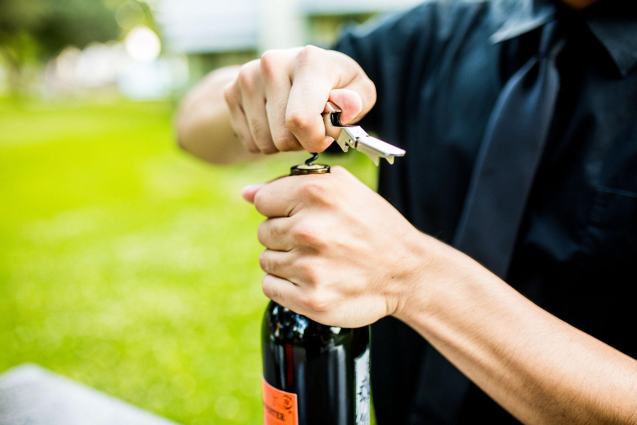 Bartender opening wine bottle