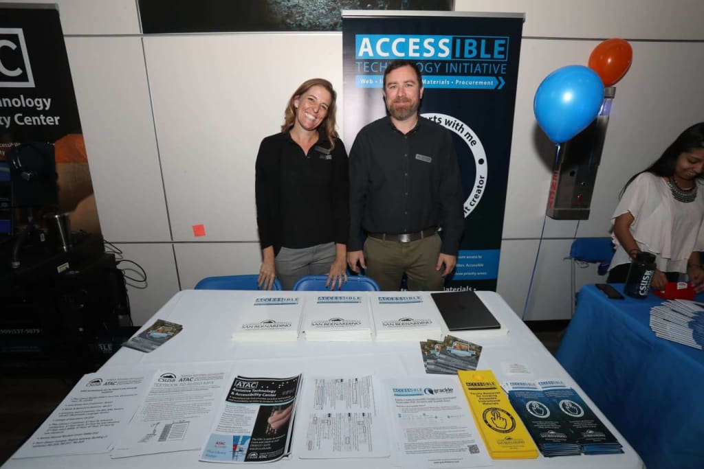 """(L to R) Christine Fundell, Accessibility Specialist and Leon McNaught, Accessible Technology Initiative Coordinator at OktoberTech – Tech Days, in """"The Cave"""", CSUSB"""
