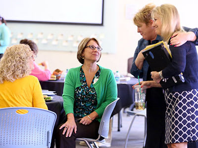 Four female teachers talking over a luncheon
