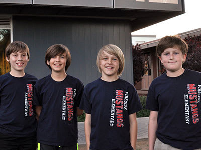 Four male students in matching shirts smiling