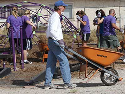 Brian Mueller pushing wheelbarrow