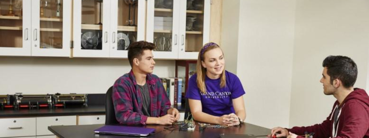 three students sitting at a desk and talking